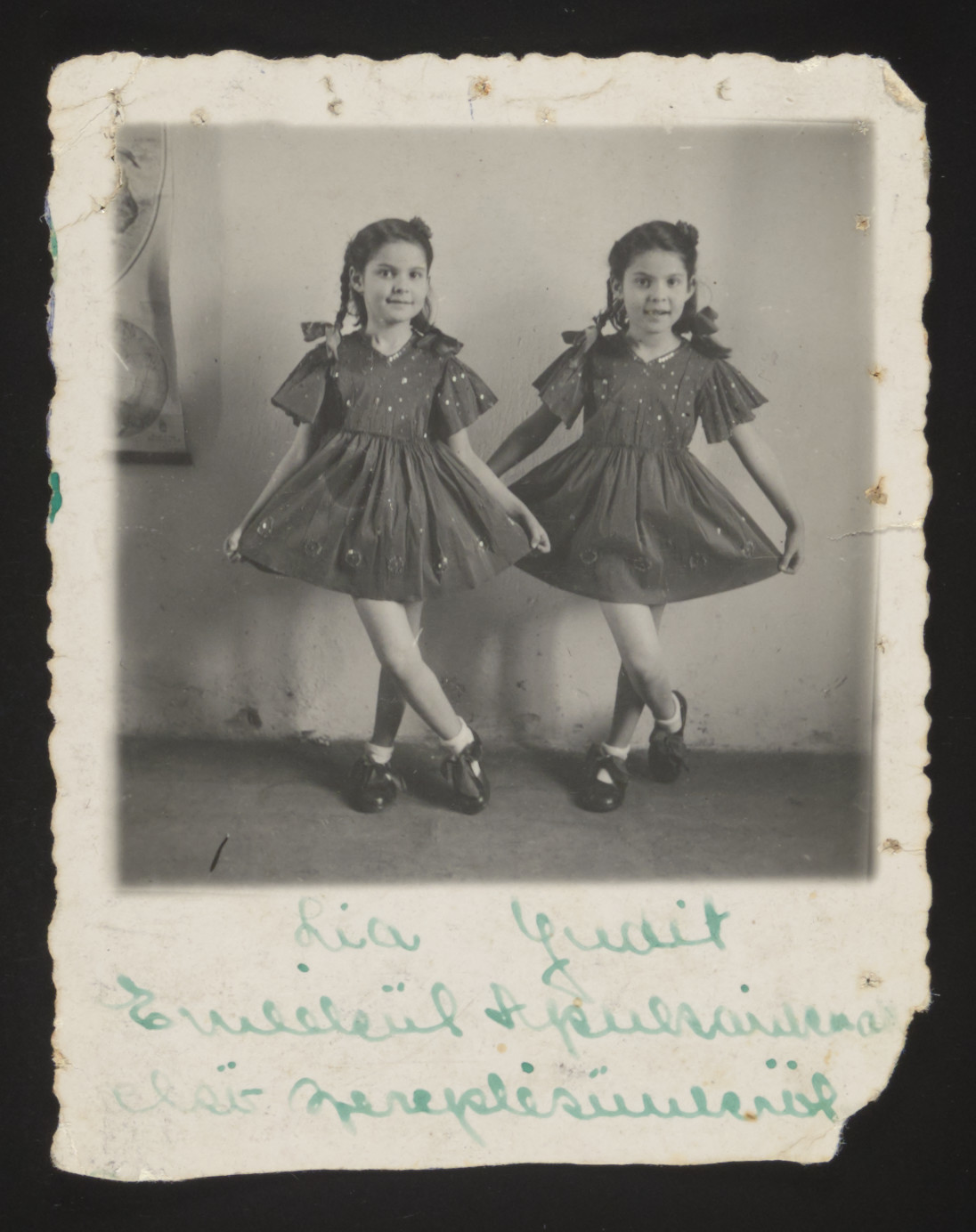 Twin sisters Yehudit and Lea pose for a Purim portrait in festive dresses.  Their mother mailed this photograph to their father in a Hungarian forced labor brigade.