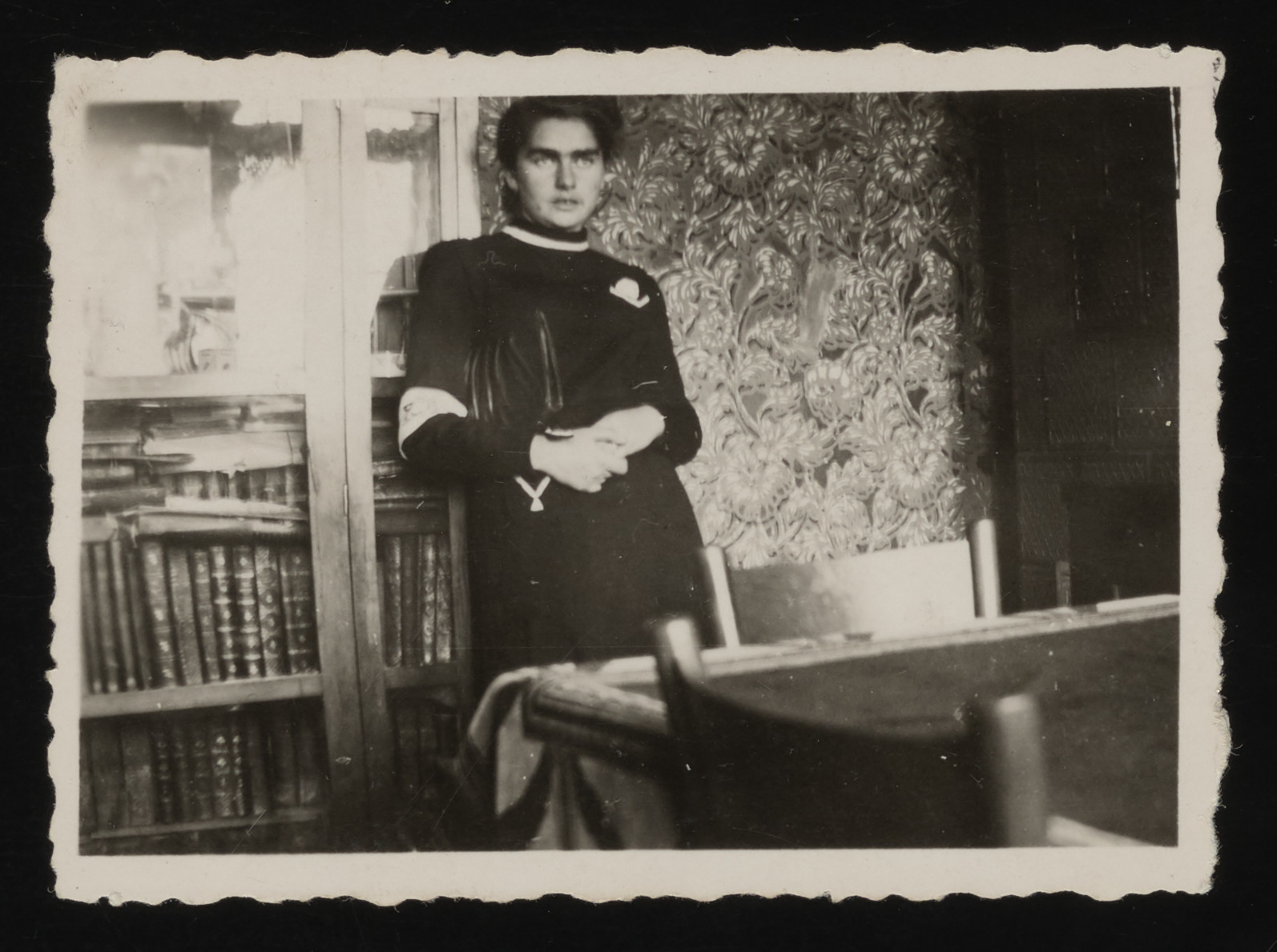 Rachel Saleschütz stands in front of a bookcase in her apartment in the Kolbuszowa ghetto.