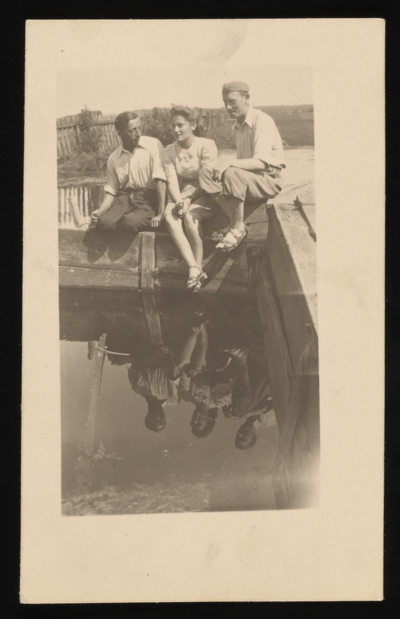 Two young men and a young woman sit near the water in the Kolbuszowa ghetto   Pictured from left to right are: Noah Huttner, Rozia Susskind, and Szmuel Weichselbaum, all friends of Naftali Saleschütz.