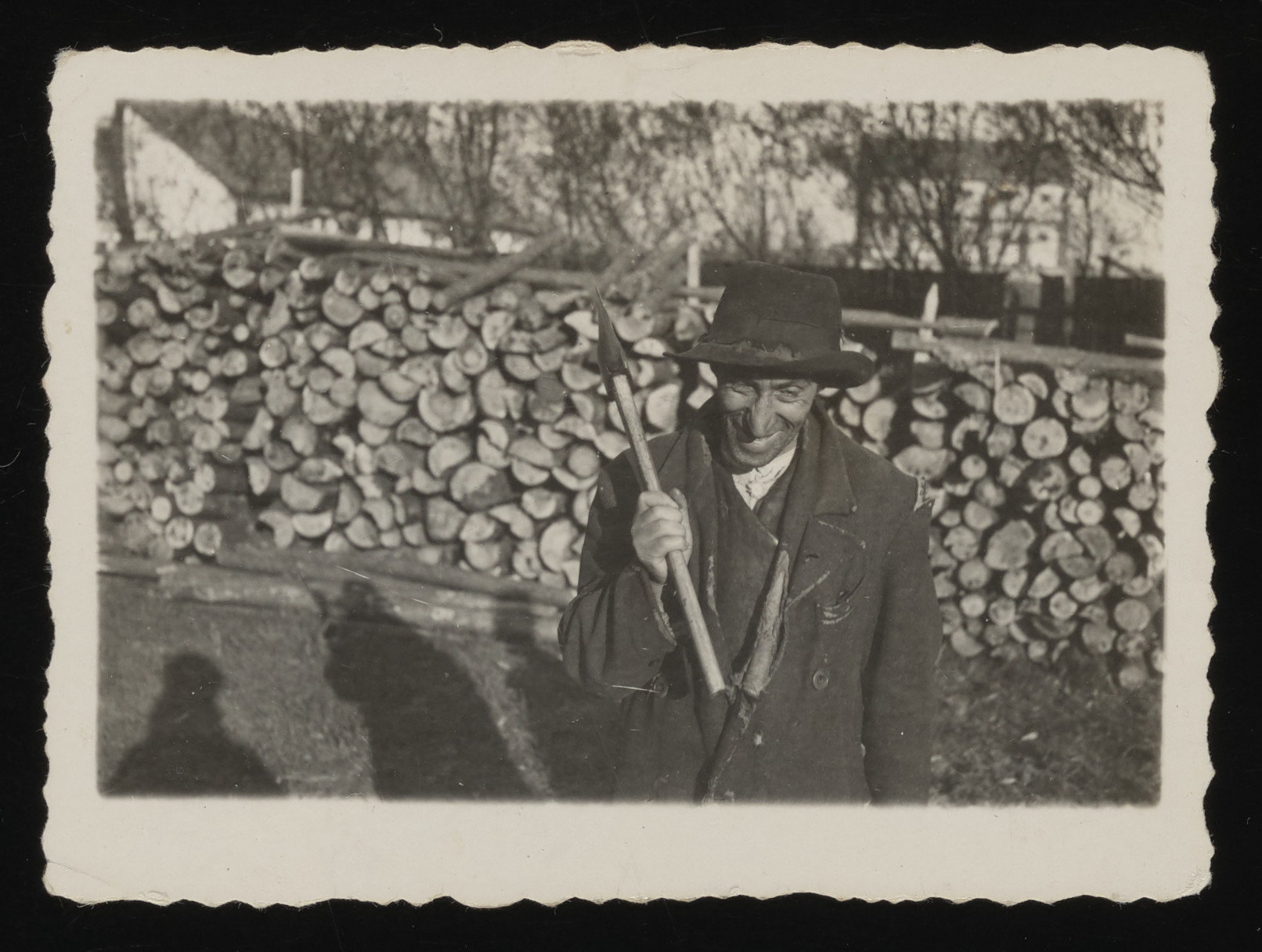 Portrait of Lejb Langweil holding an ax in front of a wood pile.    The Germans took pictures of Langweil to send home to their friends and family to show what a Jew looks like.  He worked as a cleaner at the police station. When three prominent Jews were forced to clean there, Langweil was told to supervise them. Instead, he did the work for them, saying that the work was unsuitable for men of their stature.