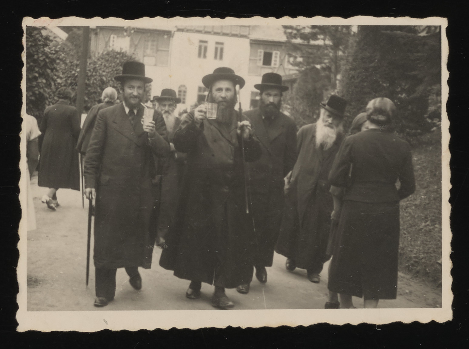 Religious Jews stroll along a street at a resort in the Tatra Mountains.    Pictured from right to left are Isak Saleschütz, Reuven Weinstein, Yisroel Spira (a cousin of Shaye David Lische), and Shaye David Lische.