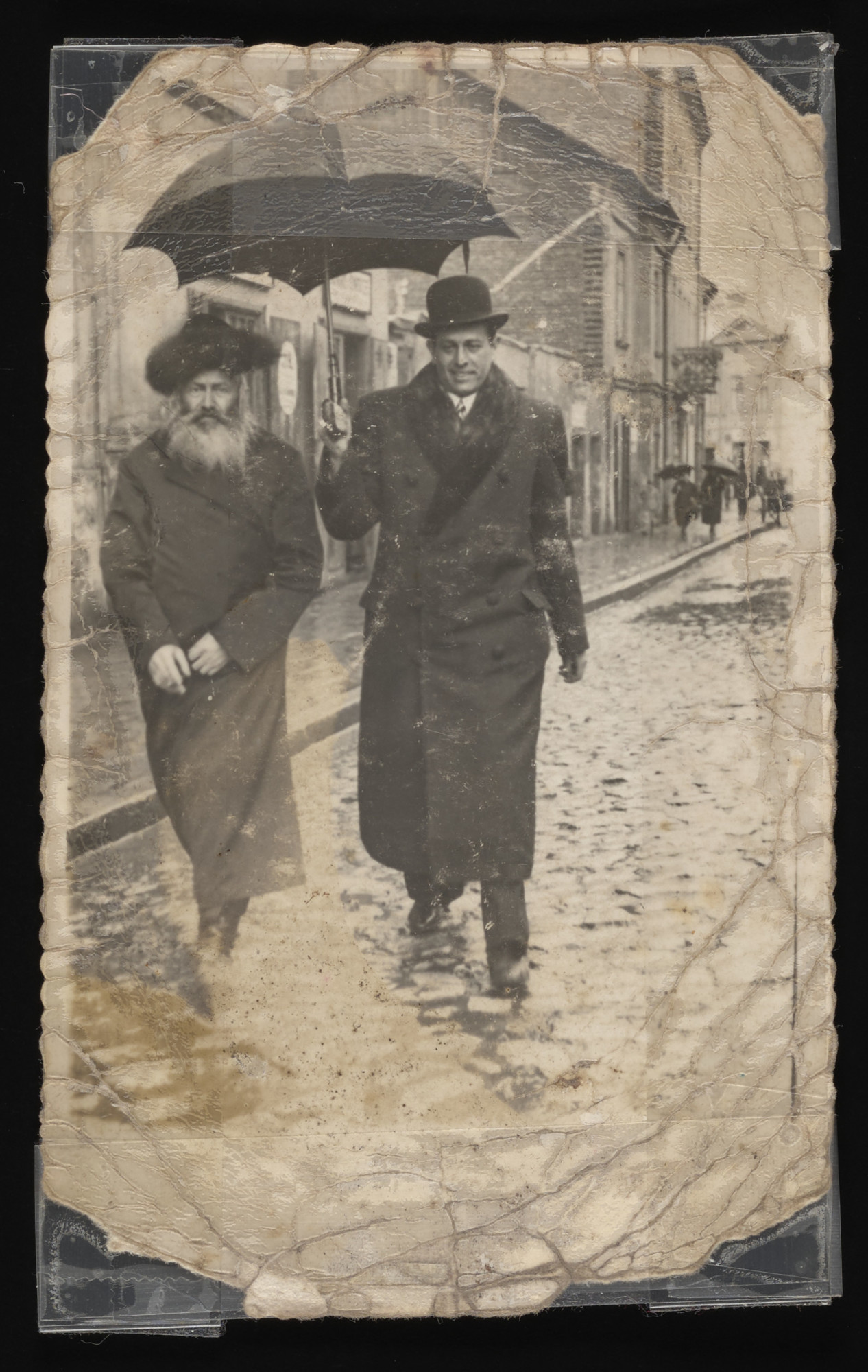 A son dressed in modern clothing holds an umbrella over his father, a Hasidic Jew named Fuchs, to protect him from the rain.