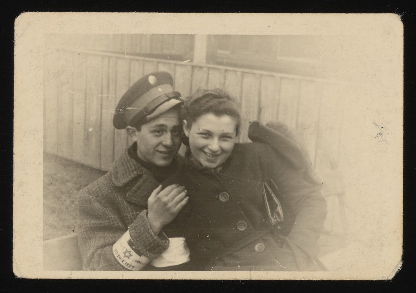 A Jewish policeman poses with his girlfriend in the Rzeszow ghetto.  Pictured is Lonek Fisz, a Jew from Kolbuszowa, who was a member of the Jewish police in Rzeszow.  Lonek was caught forging passports for forty Jews who were trying to escape to Hungary.  He was killed by the Gestapo on September 12, 1942, in Nowawies along with 200 other Jews.  Naftali Saleschütz found this picture in Fisch's jacket after he was shot.