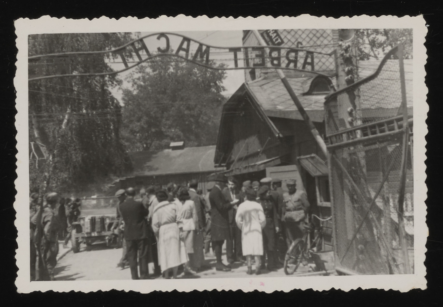 """Members of an international commission of inquiry are gathered beneath the """"Arbeit Macht Frei"""" sign at the entrance to Auschwitz."""