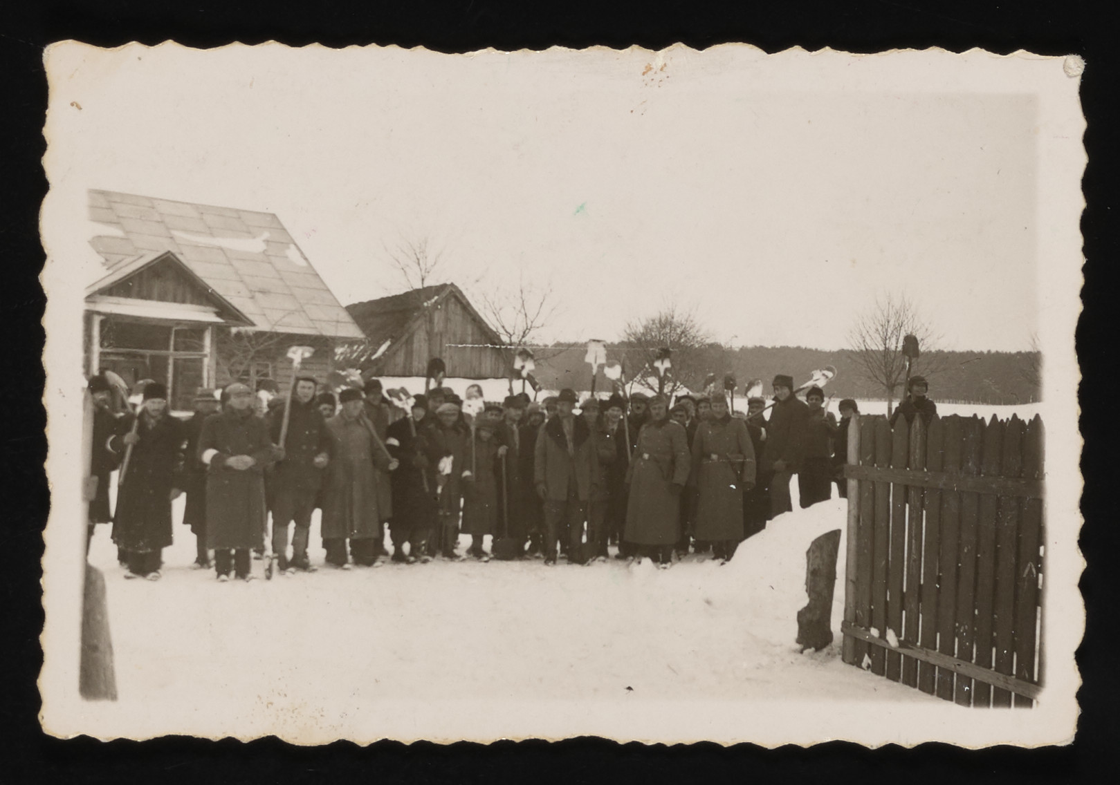 A group of Jewish forced laborers pose with shovels at the entrance to the Kolbuszowa ghetto.