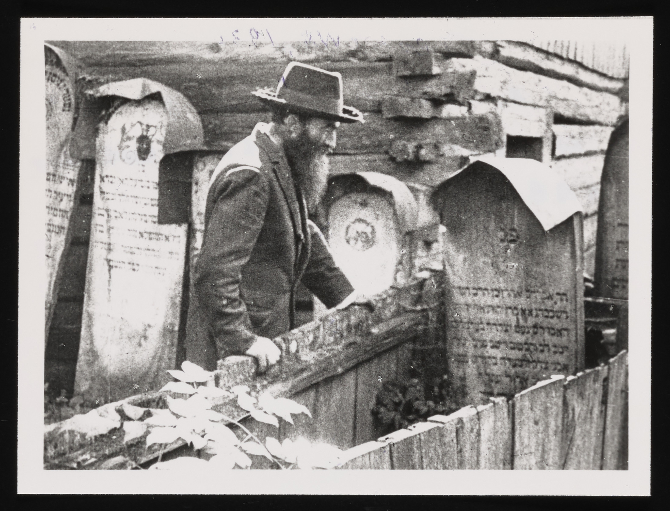 """Avrum Polimer visits the grave of the former rebbe of  Kolbuszowa, known as the """"alter rebbe,"""" in the Kolbuszowa cemetery."""