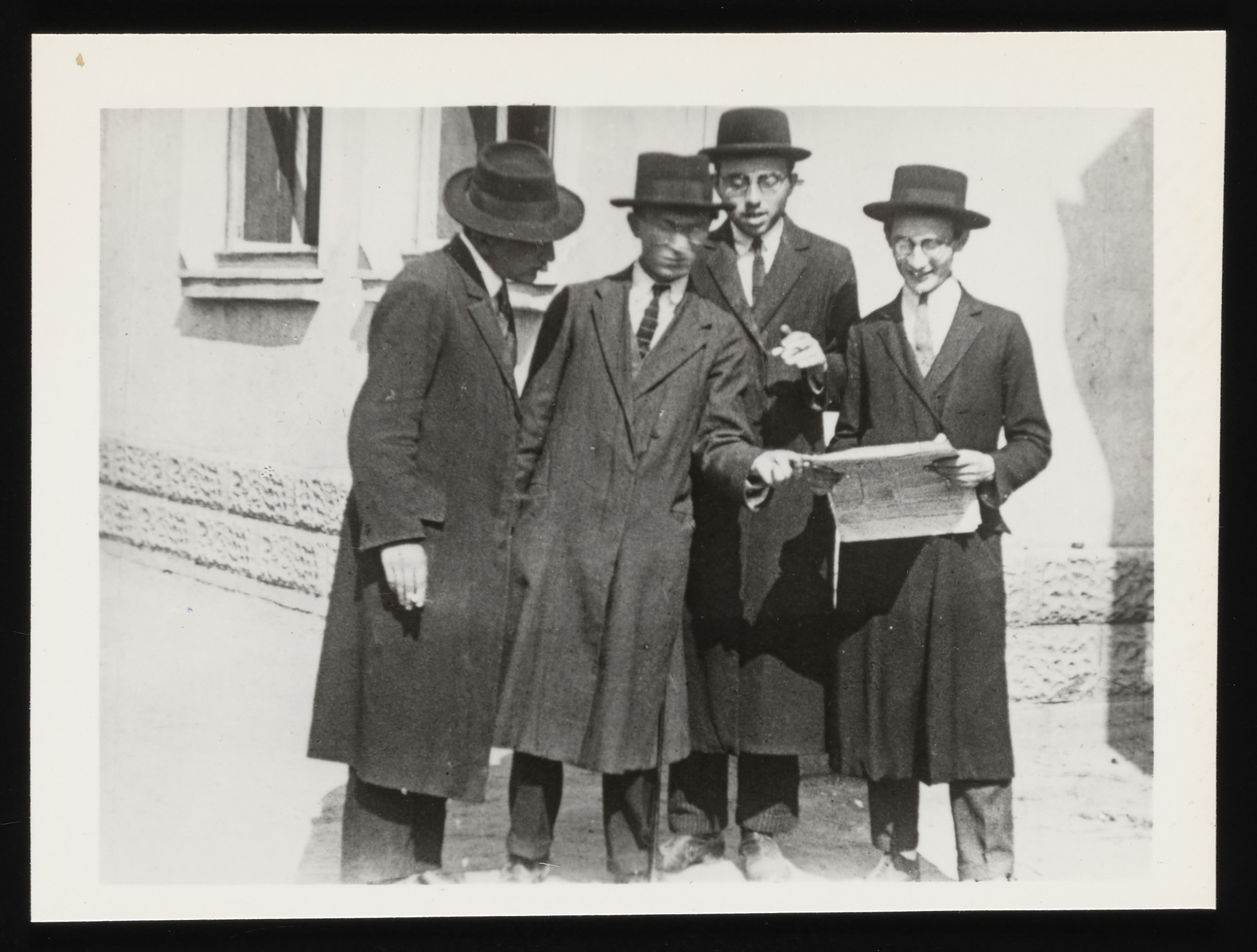 Four young Jewish religious men read a newspaper on a street corner in Kolbuszowa.  Pictured from right to left: (unknown), Meilech Kirshenbaum, (unknown), and Mordechai Israelowicz.