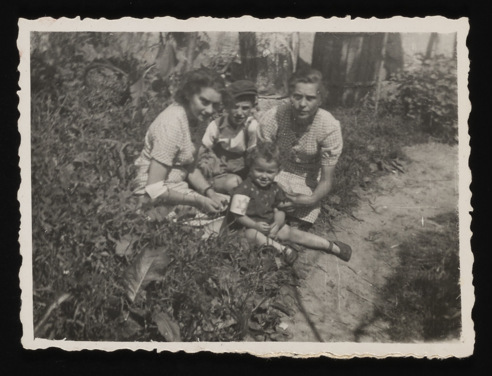 Members of the Saleschütz family sit in the grass in the Kolbuszowa ghetto.    Pictured are Rachel (left) and Matla (right) Saleschütz.  Seated between them are their niece and nephew, Blimcia (front) and Shulim (behind).