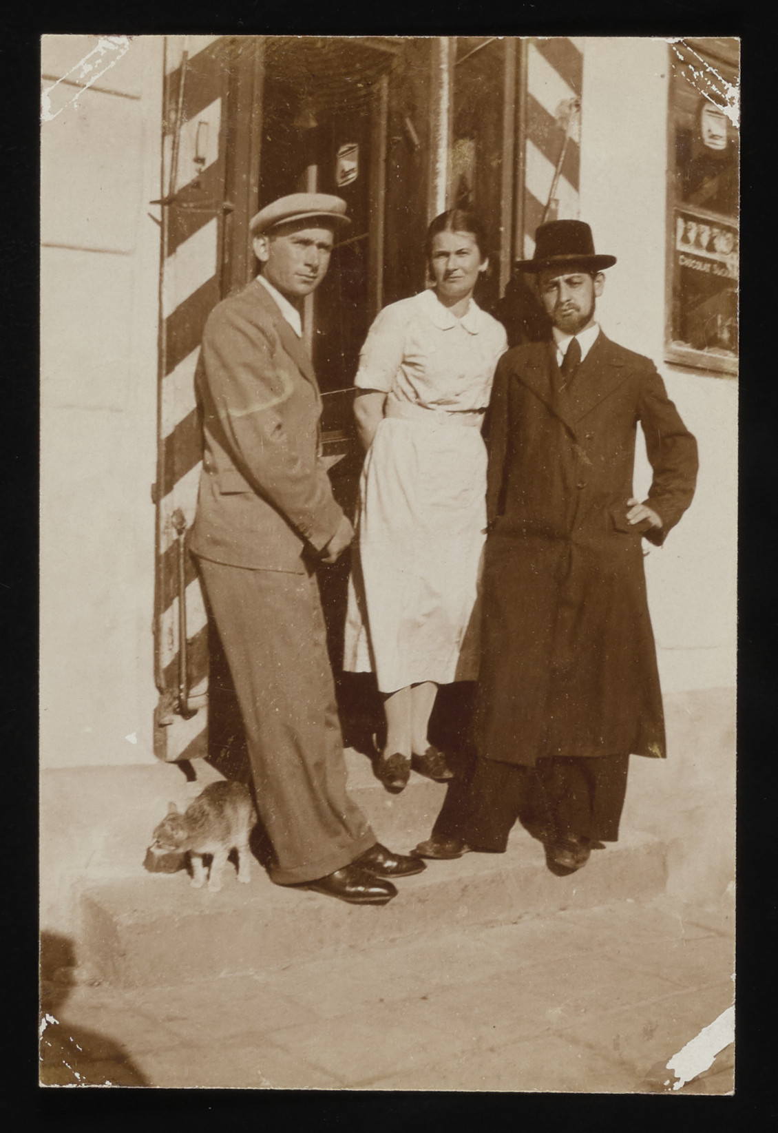 David Saleschütz (left) poses in front of a store with his sister, Liba and her husband Moshe Kornfeld during a visit home from Palestine.