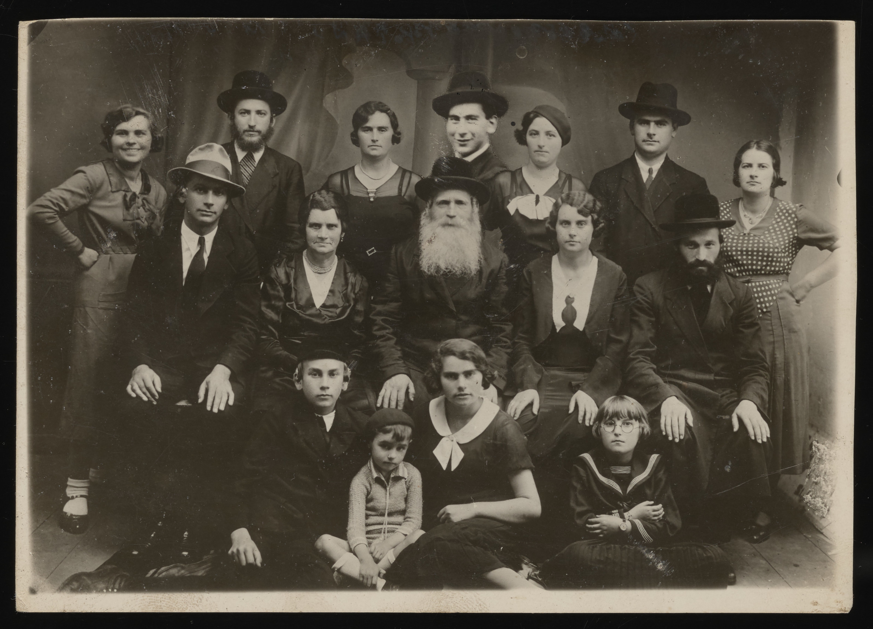 Studio portrait of the Saleschütz family taken during the visit of the older son, Avrum, from the United States.  Pictured in the front row from left to right are: Naftali, Shulem and Rachel Saleschütz; and Shaindel Weinstein.  In the middle row from left to right are: Avrum,  Esther and Isak Saleschütz; and Bluma Gela and Reuven Weinstein. Standing in the back row from left to right are: Matla Saleschütz, Shaye David and Malcia Lische; David Saleschütz; Hannah and Leibush Saleschütz; and Liba Saleschütz.  David's picture was pasted in because he was living in Palestine.