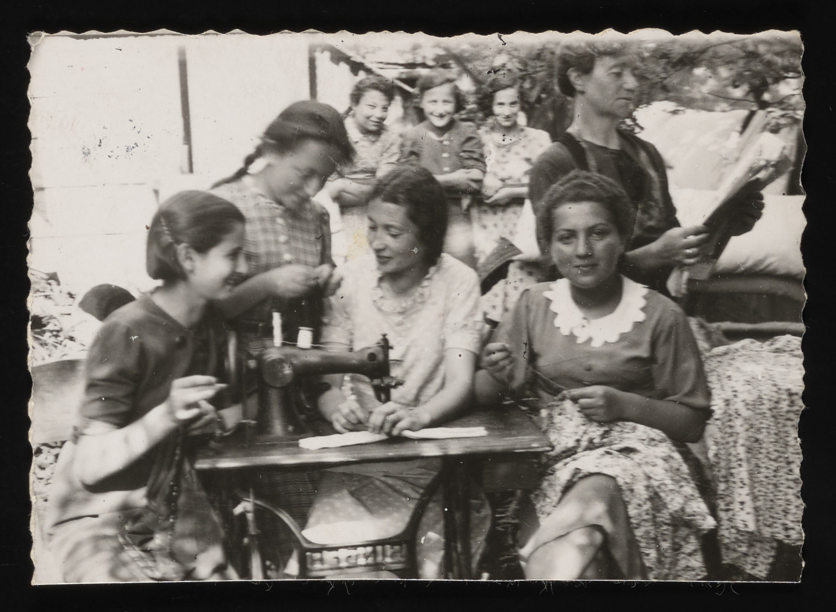 A group of Jewish girls attend a sewing class in Kolbuszowa.  Seated left to right are Wiesenfeld, a Polish girl, and Genia Nussbaum.  Standing on the right is the teacher.