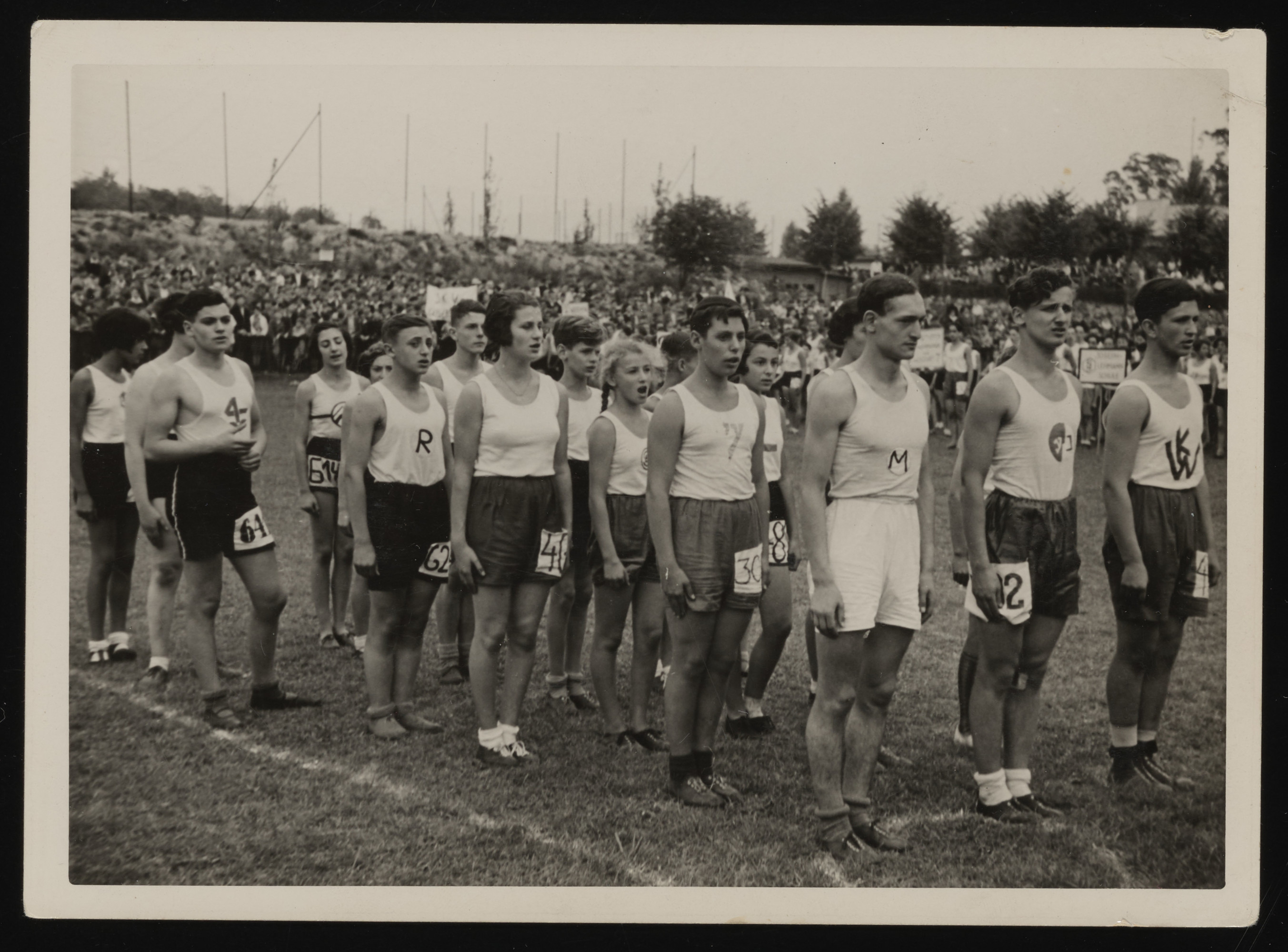 Students from various Jewish schools in Berlin gather to sing Hatikva at a large track and field event.