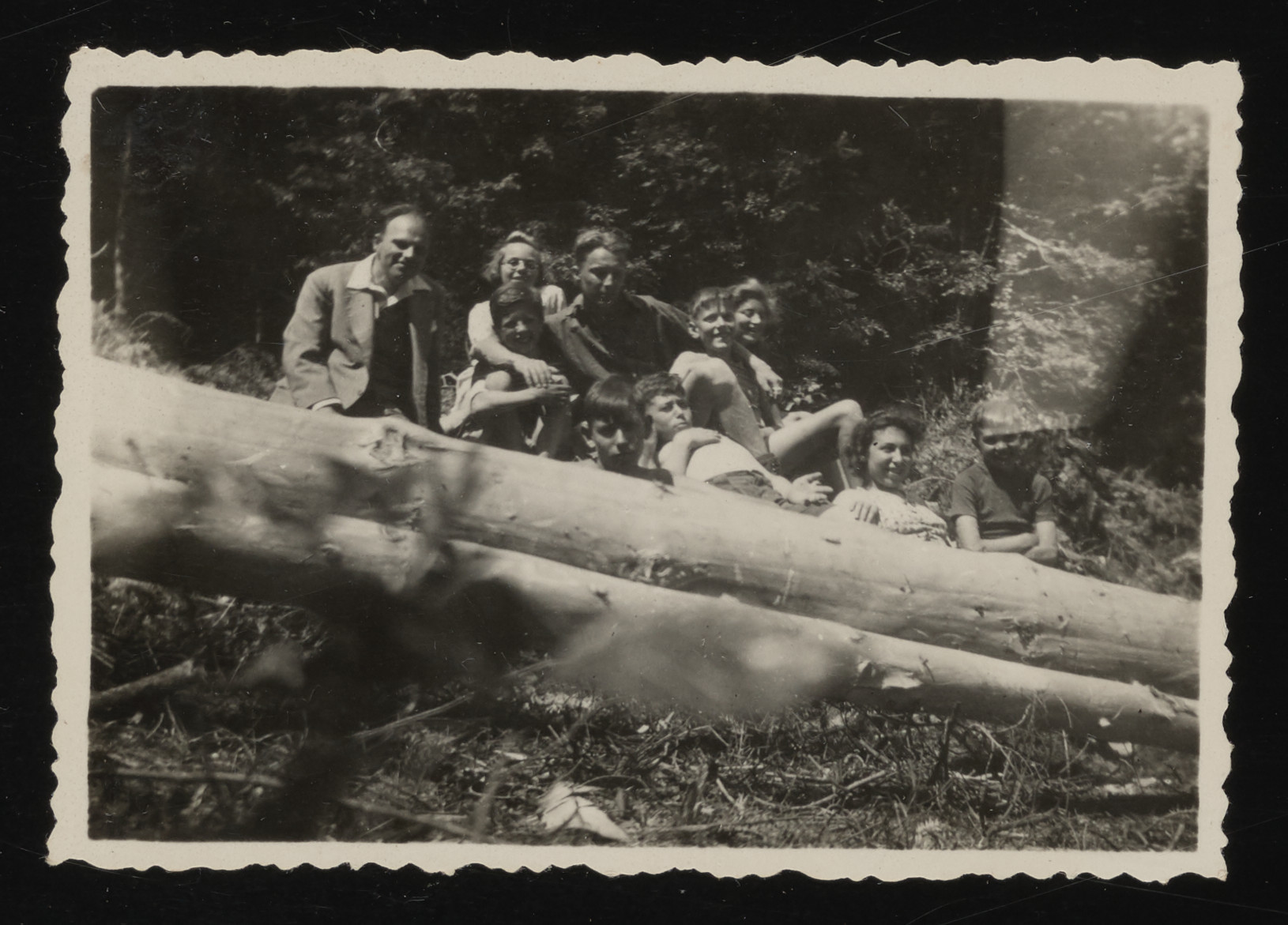 Jewish youth who are living in hiding in Le Chambon sit next to a fallen tree.