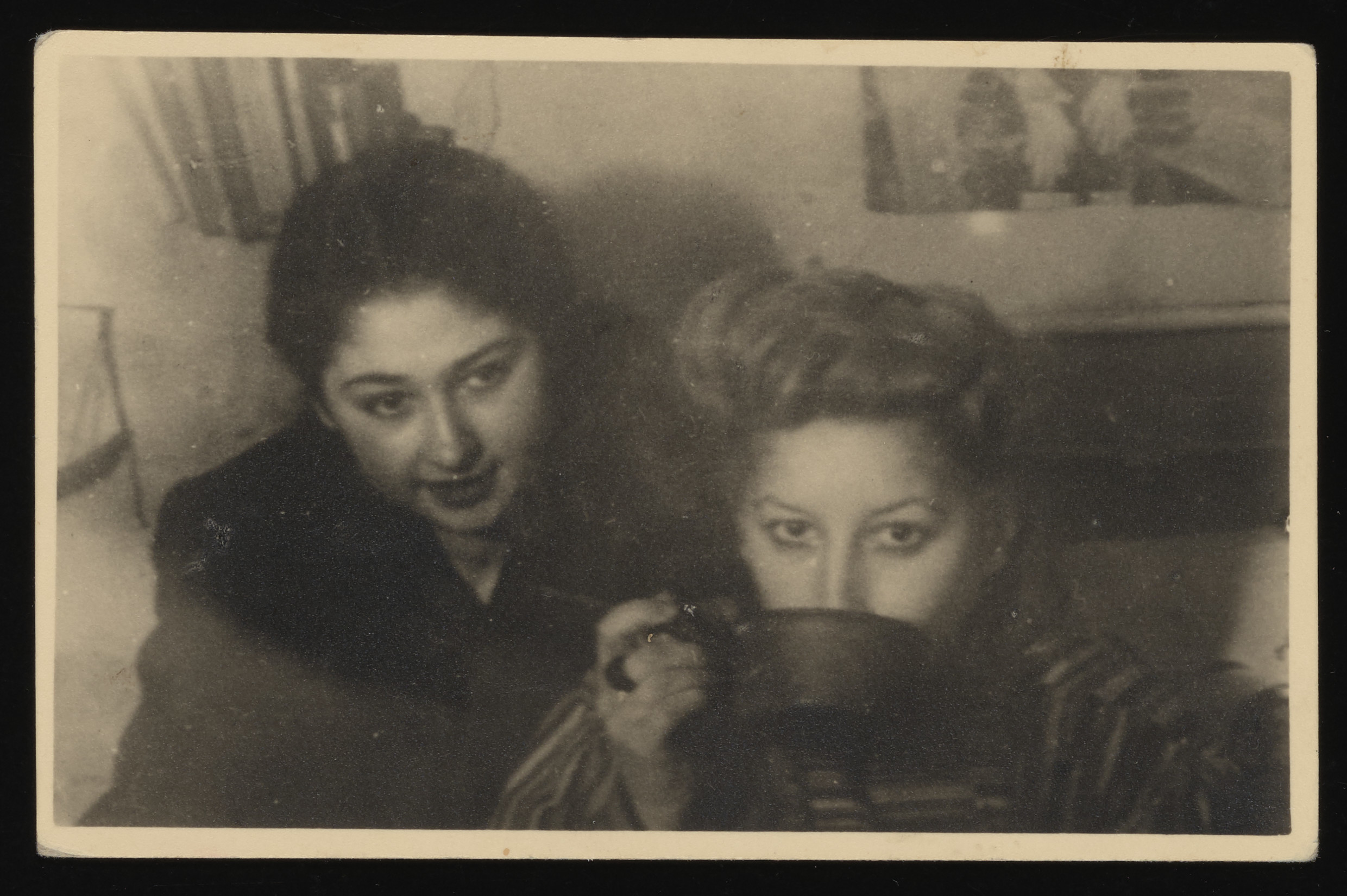 Close-up portrait of two women, one of whom is drinking from a large mug, in the Lodz ghetto.  Pictured are Helena Zemler (left) and Melania Fogelbaum (right).