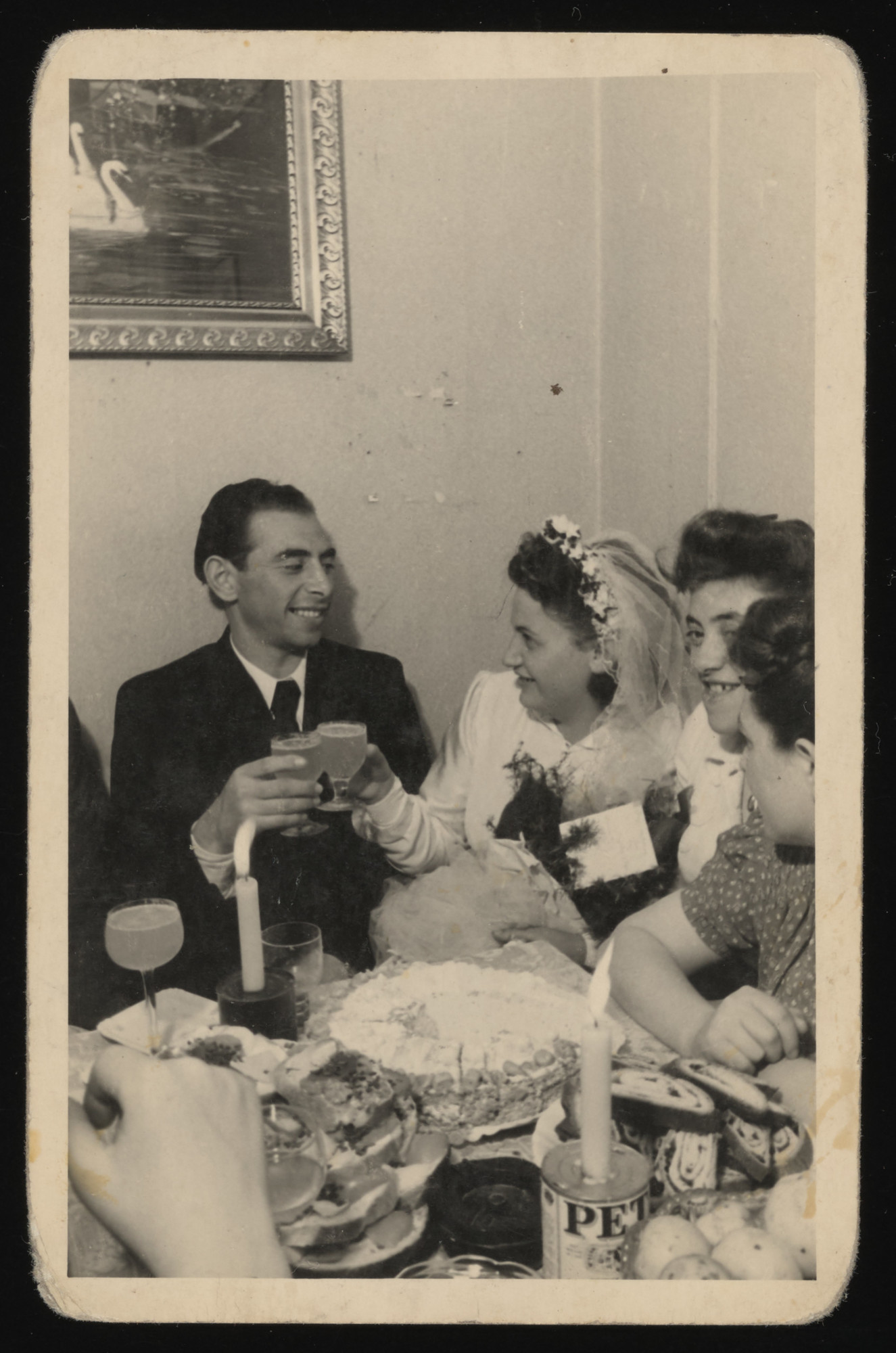 A bride and groom toast one another at a dinner in the Zeilsheim displaced persons camp.   Makeshift candlestick holders fashioned from PET milkcans adorn the table.  The couple's ketuba identifies them as Yaakov Mordechai ben Aaron and Rachel bat Efraim.