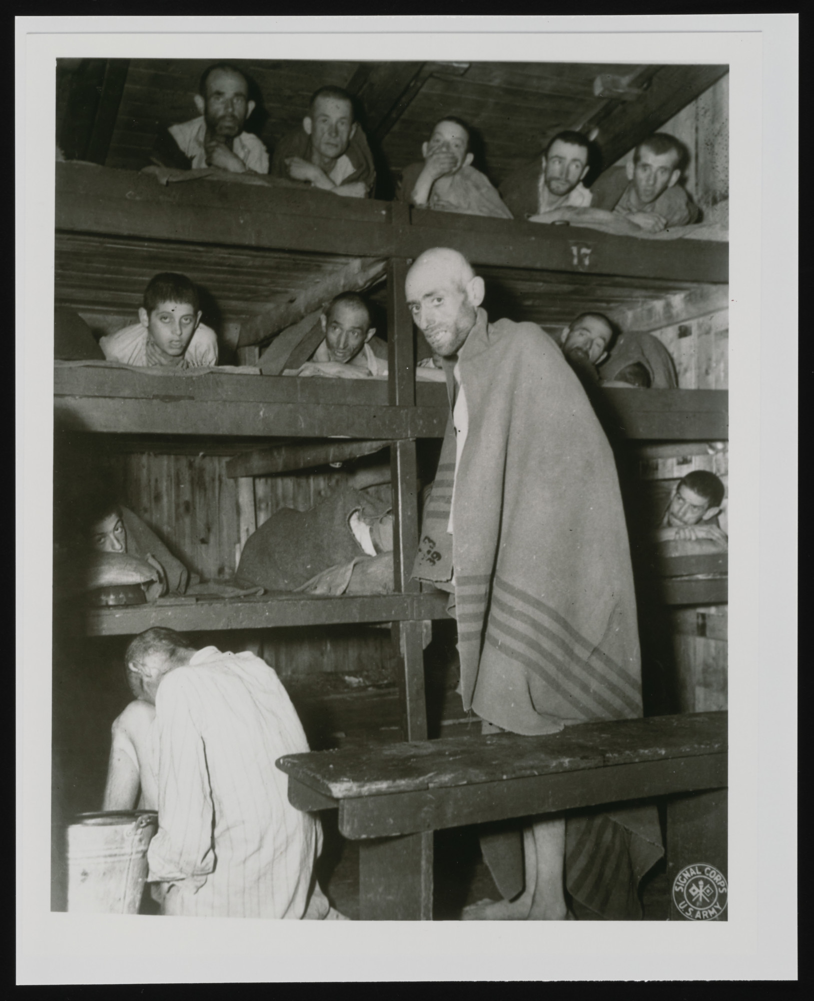 """Survivors lie in multi-tiered bunks in a barracks in the newly liberated Buchenwald concentration camp.  The original caption reads, """"Men and young boys showing the way and manner in which they slept every night for the last three years at the camp near Weimar Germany."""" [sic]  According to the Signal Corps caption, the photo was taken on April 14, 1945."""