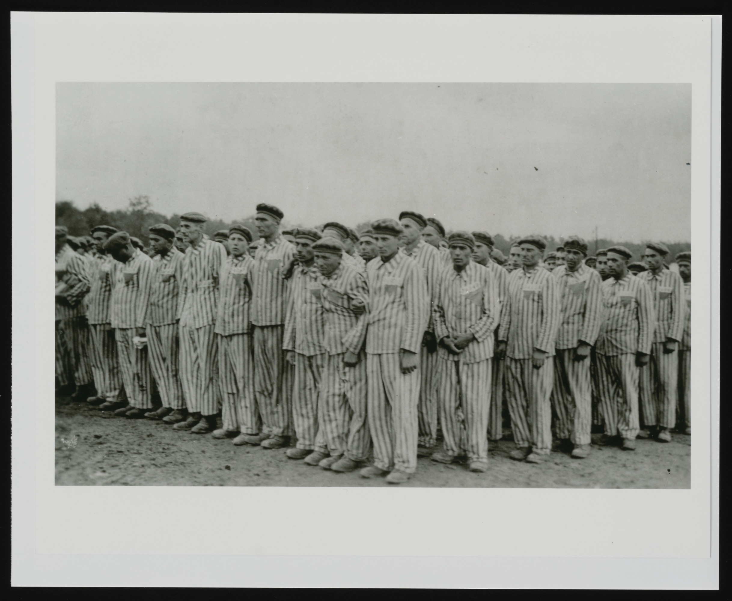 Prisoners standing during a roll call.  Each wears a striped hat and uniform bearing colored, triangular badges and identification numbers.