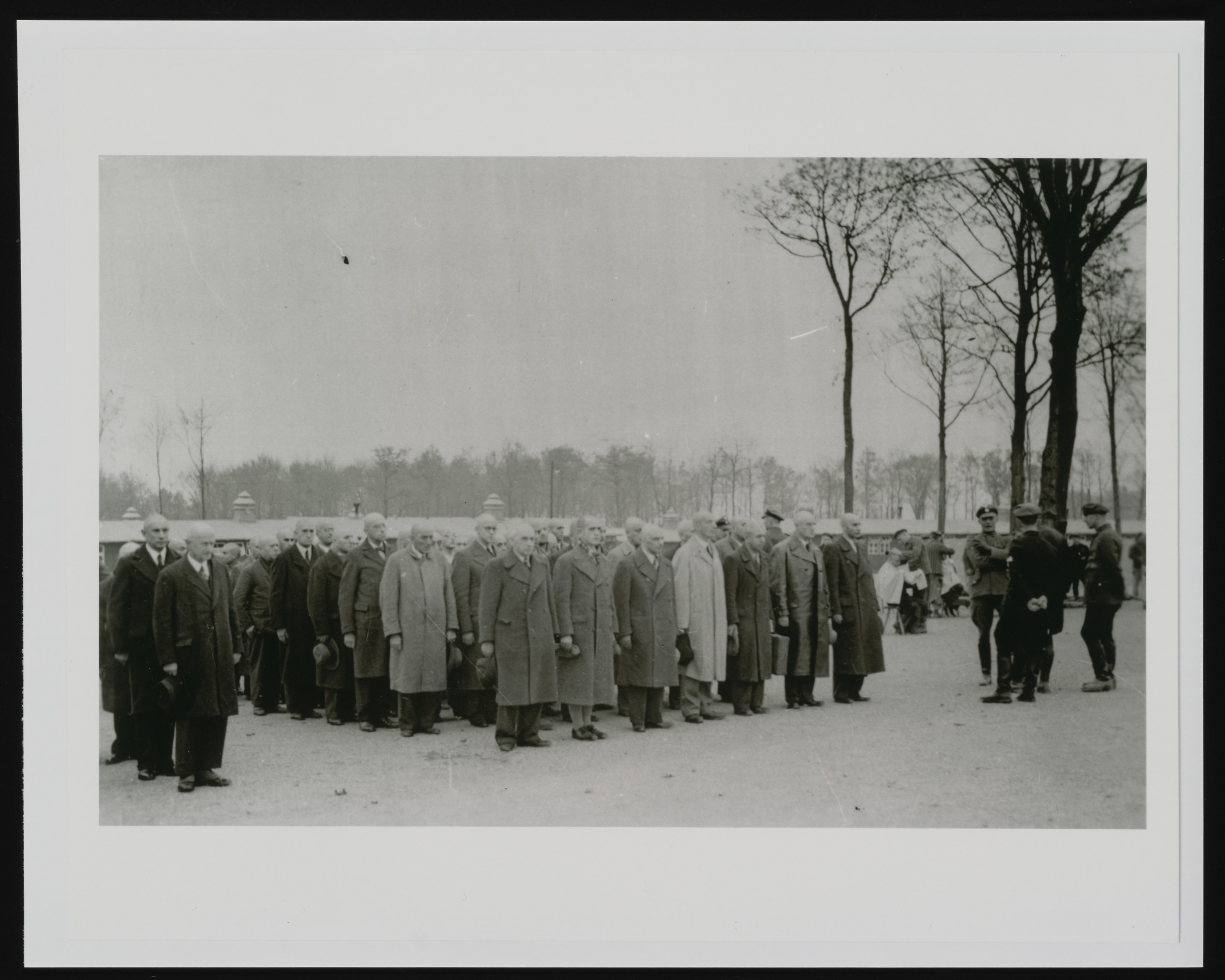 Newly arrived prisoners, still in their civilian clothes, and after shaving and disinfection, stand at roll call in Buchenwald concentration camp shortly after Kristallnacht.