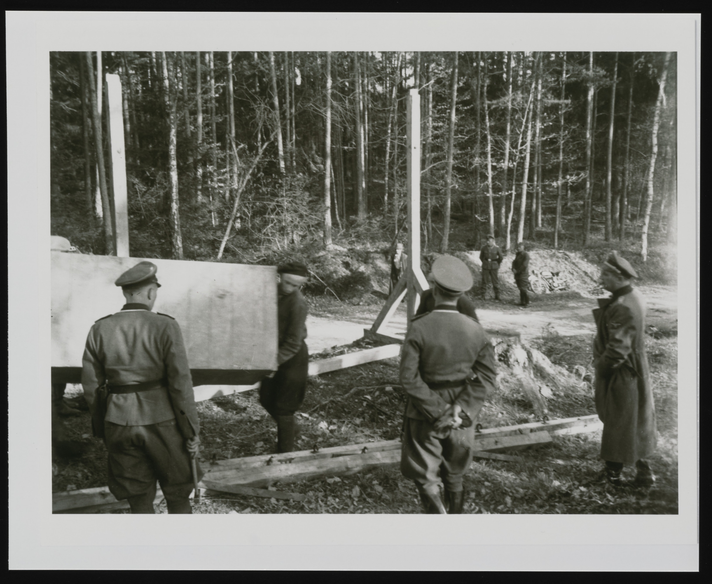 SS officers supervising the building of a gallows in the forest near Buchenwald concentration camp.
