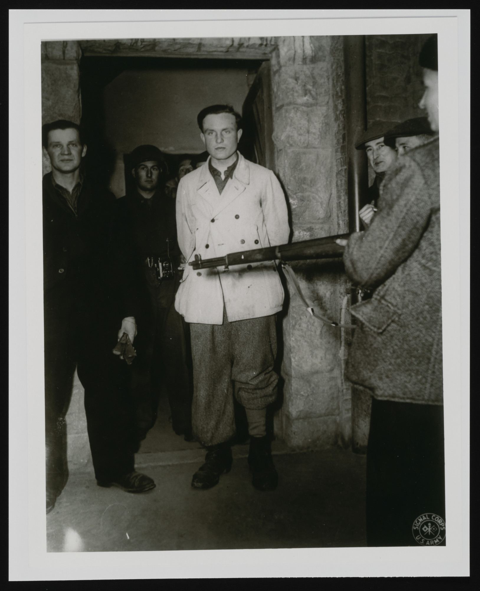 Armed survivors in Buchenwald hold two German guards(?) at gunpoint as an American soldier looks on.