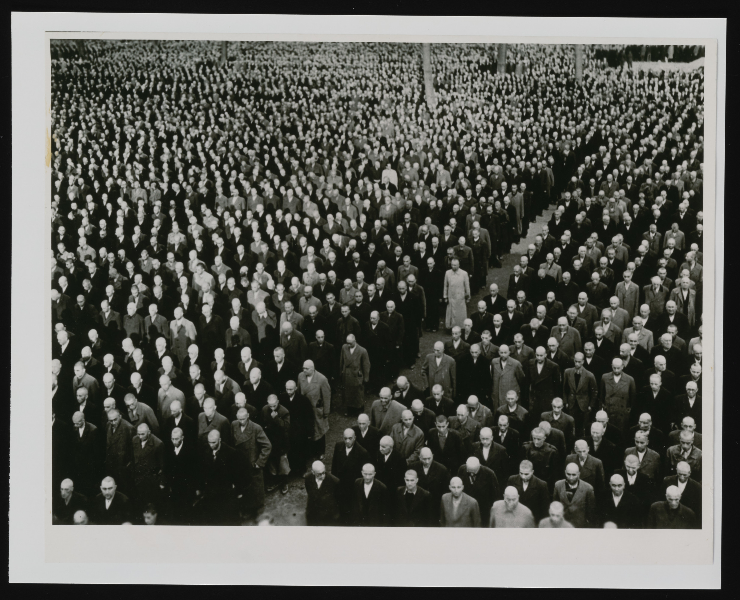 Newly arrived prisoners, with shaven-heads, stand at attention in their civilian clothes during a roll call in the Buchenwald concentration camp.    Some still have their valises and other luggage with them.  These prisoners were among the more than 10,000 German-Jews who were arrested during the Kristallnacht pogrom (November 9-10, 1938) and sent to Buchenwald.  Another 20,000 German-Jews arrested at the same time were imprisoned in Dachau and Sachsenhausen.
