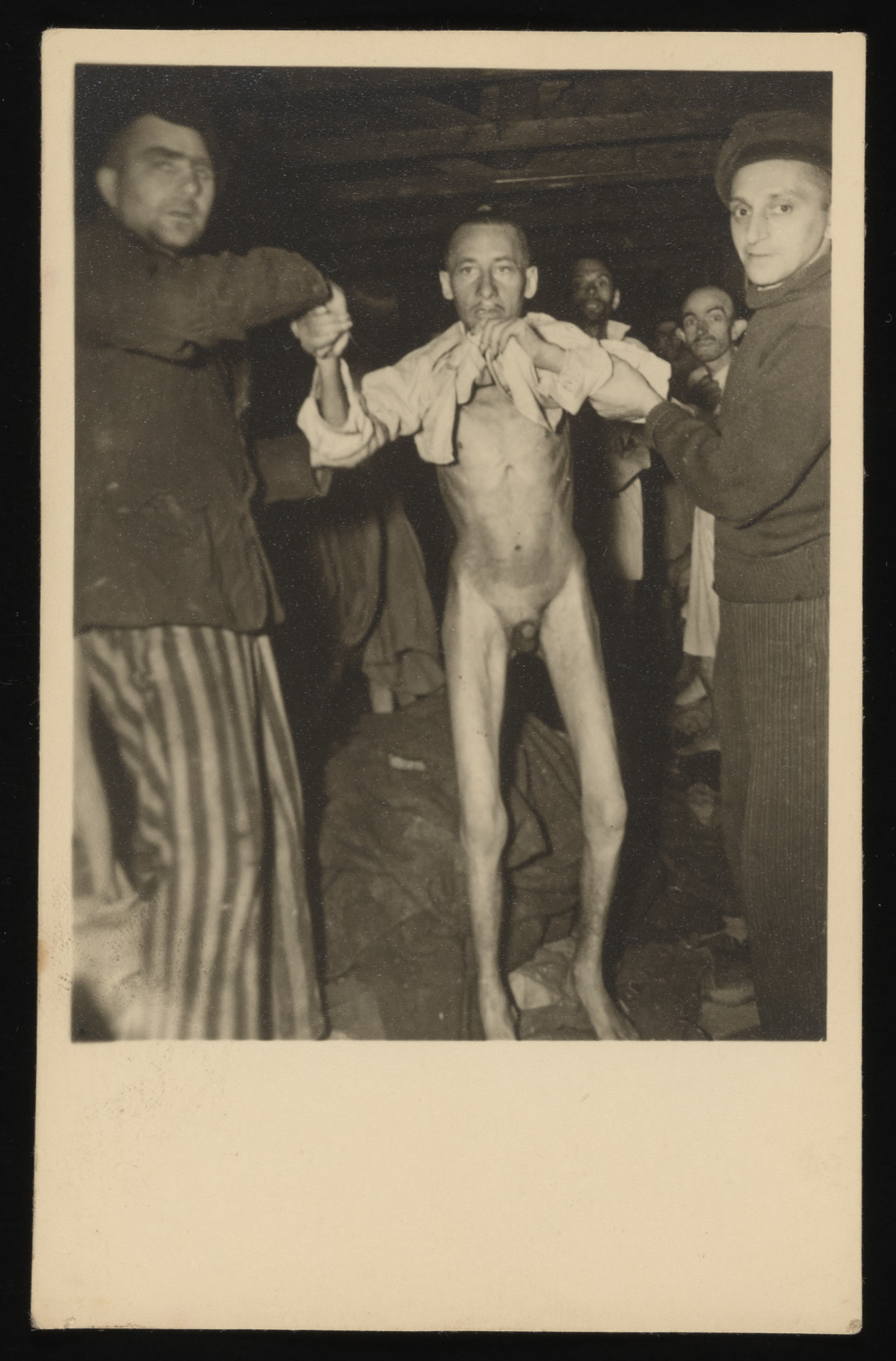 """Assisted by two other men, a survivor holds up his shirt to display his emaciated condition in the newly liberated Buchenwald concentration camp.  The original caption reads, """"This man being helped along by his frends is so weak from the lack of food that he can hardly walk. One of the many hundreds in the same condition at the cap of Weimar Germany."""" [sic]  According to the Signal Corps caption, the photo was taken on April 14, 1945."""
