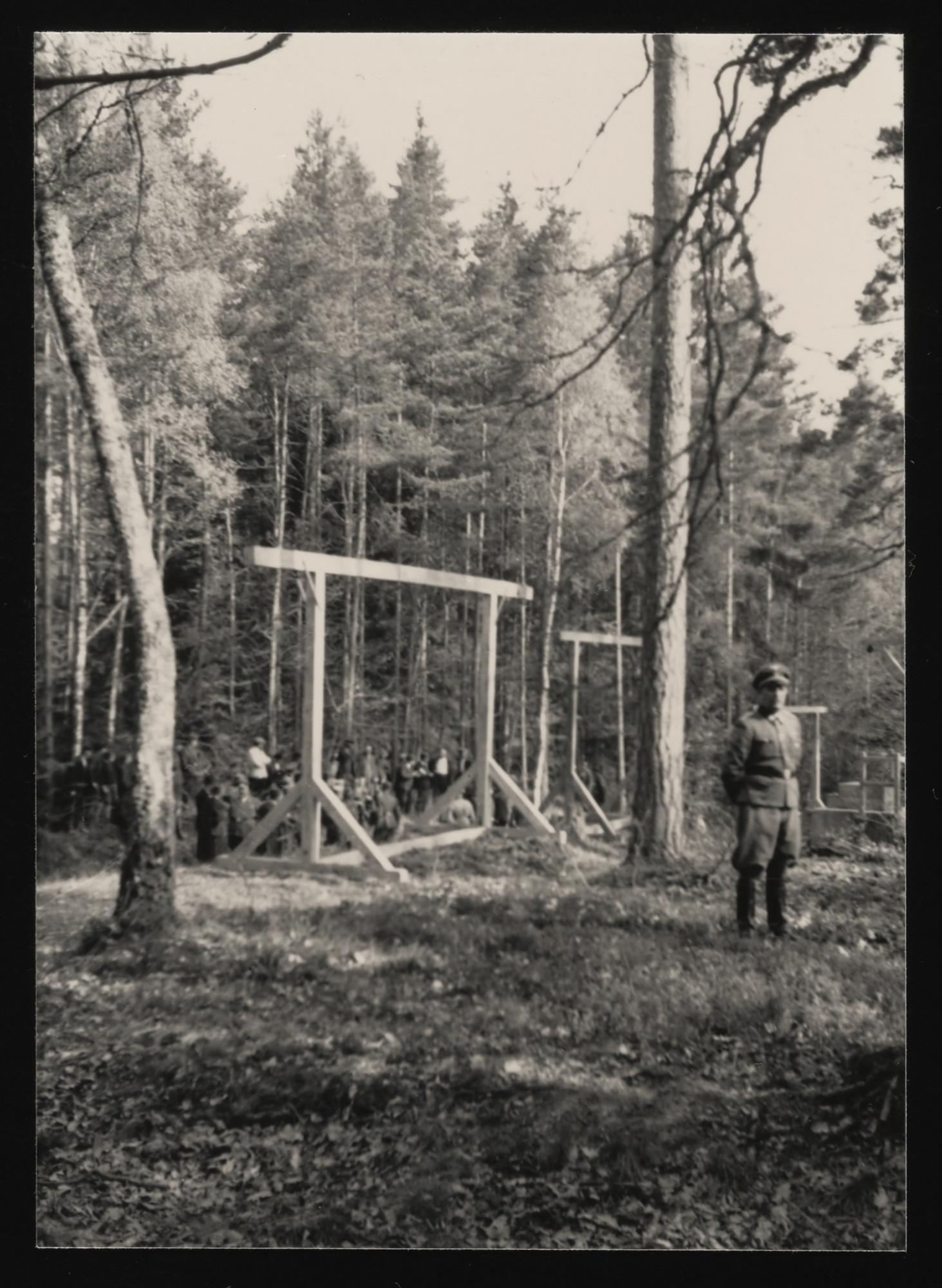 An SS officer standing in front of a newly constructed gallows in the forest near Buchenwald concentration camp.