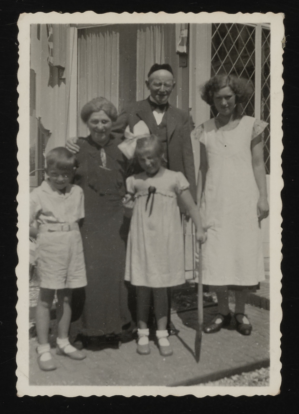 Two Jewish children pose with their grandparents outside their home in Amsterdam.  Pictured are Leo and Bertie Serphos and Levi and Grietje Koppels. The woman on the right was assisting the Koppels.