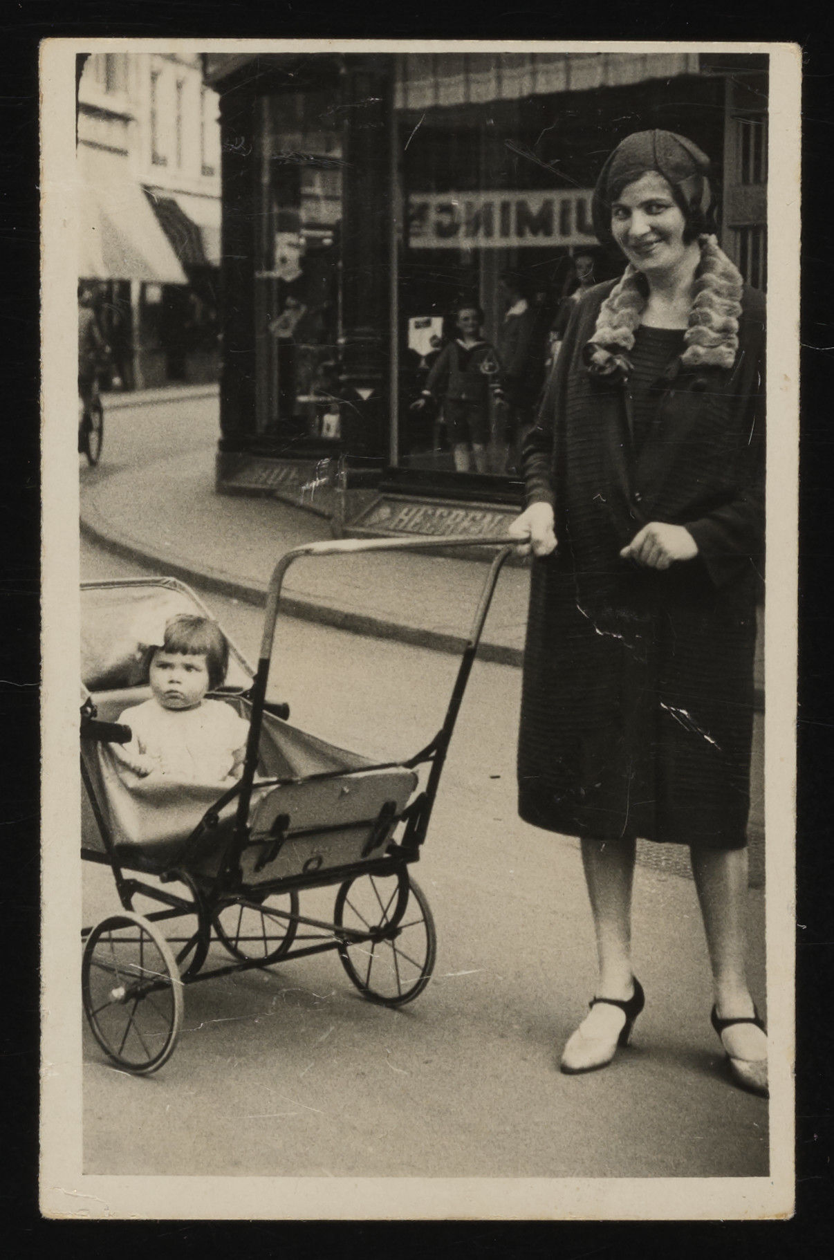 A mother poses for a street photograph with her baby daughter in a stroller, outside a store in Amsterdam.  Pictured are Benjamina and Bertie Serphos.
