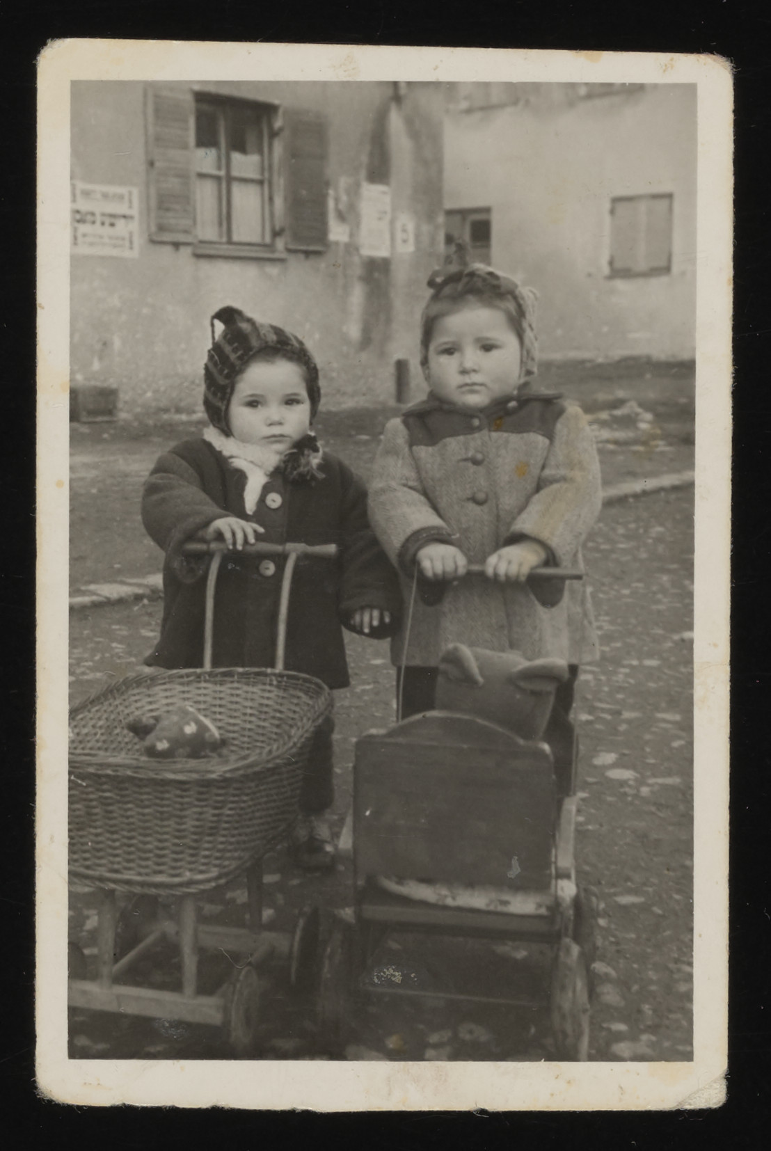 Two children push toy carriages at the Foehrenwald DP camp.    The girl on the left is Sara Winiger.