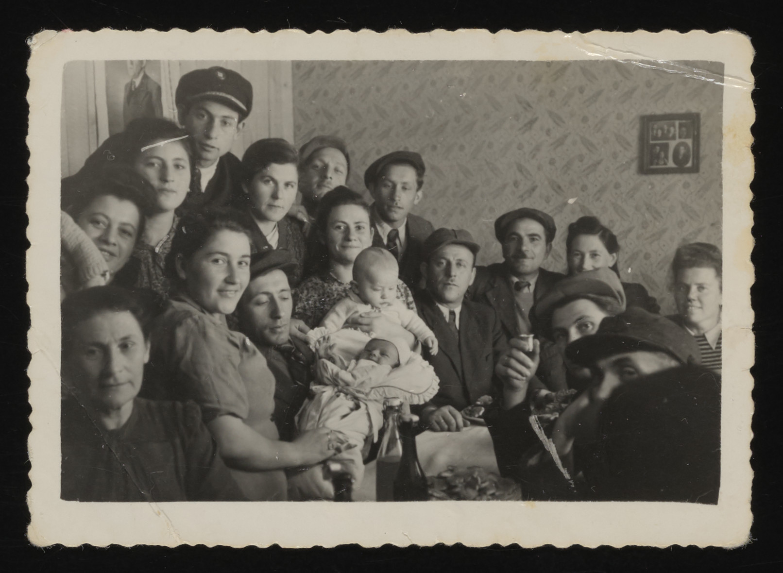 Jewish DPs gather in an apartment in the Foehrenwald displaced persons camp.   The event is thought to have been a joint bris for the two baby boys.  Among those pictured are Carl Nadler, holding his son David Nadler; Max Julian (now Jules) Weinsieder (baby on the right); Bernard Weinsieder (to the right of the babies); Abraham Winiger (foreground, right), Mr. and Mrs. Tony Haberman (the couple nearest the picture on the wall), Mina Winiger (third person from the left in the back row), and Abraham Lew (back row, second from right).