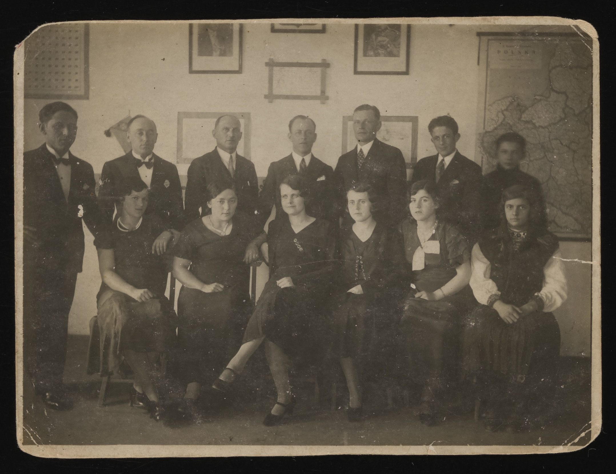 Group portrait of Polish Jews in a classroom decorated with maps and photographs.  Among those pictured are Mina Handel and her brother Hersch.  Mina is pictured seated second from the right and her brother is directly behind her.  Also pictured is Bernard Weinsieder (back row, fourth from left).