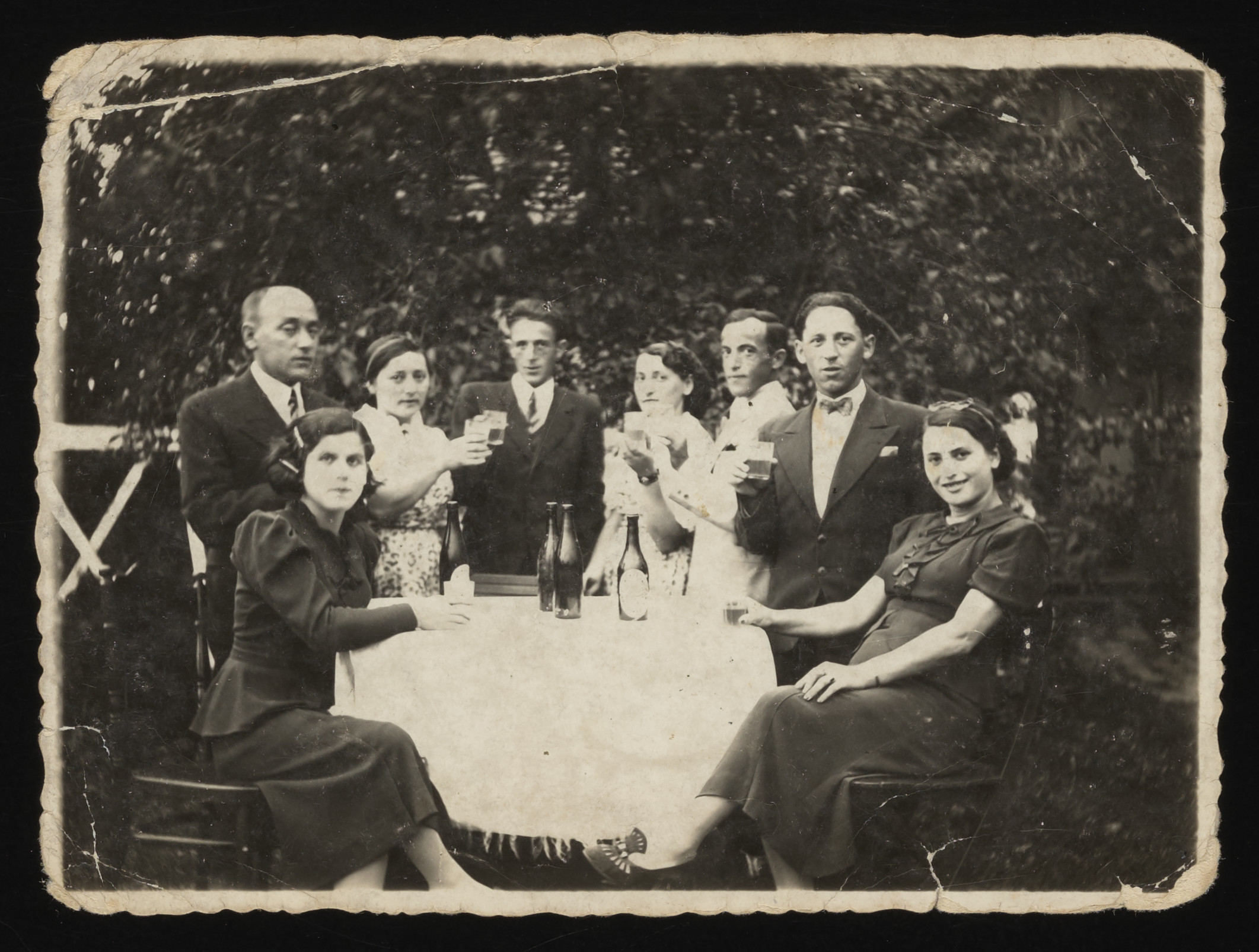 Members of a Jewish family pose around a table outdoors and offer a celebratory toast.  Among those pictured are Mina Handel at the far left and her brother Hersh, pictured fourth from the left.