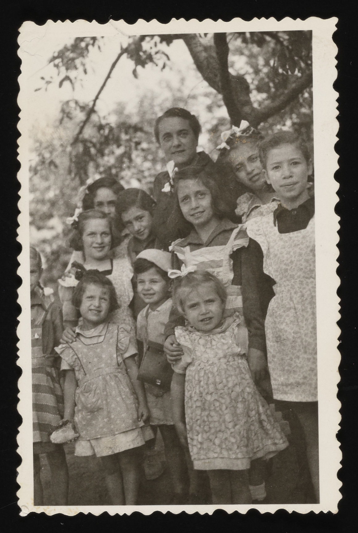 Group portrait of children in a Zionist orphanage outside of Budapest.  Pictured in the back is the director, Zsofi Brunn.