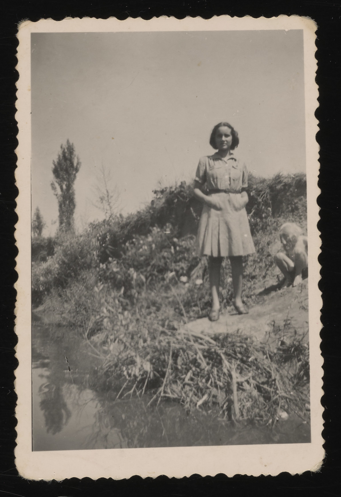 Anna Brunn, a Hungarian Jewish teenage girl, stands next to a river.