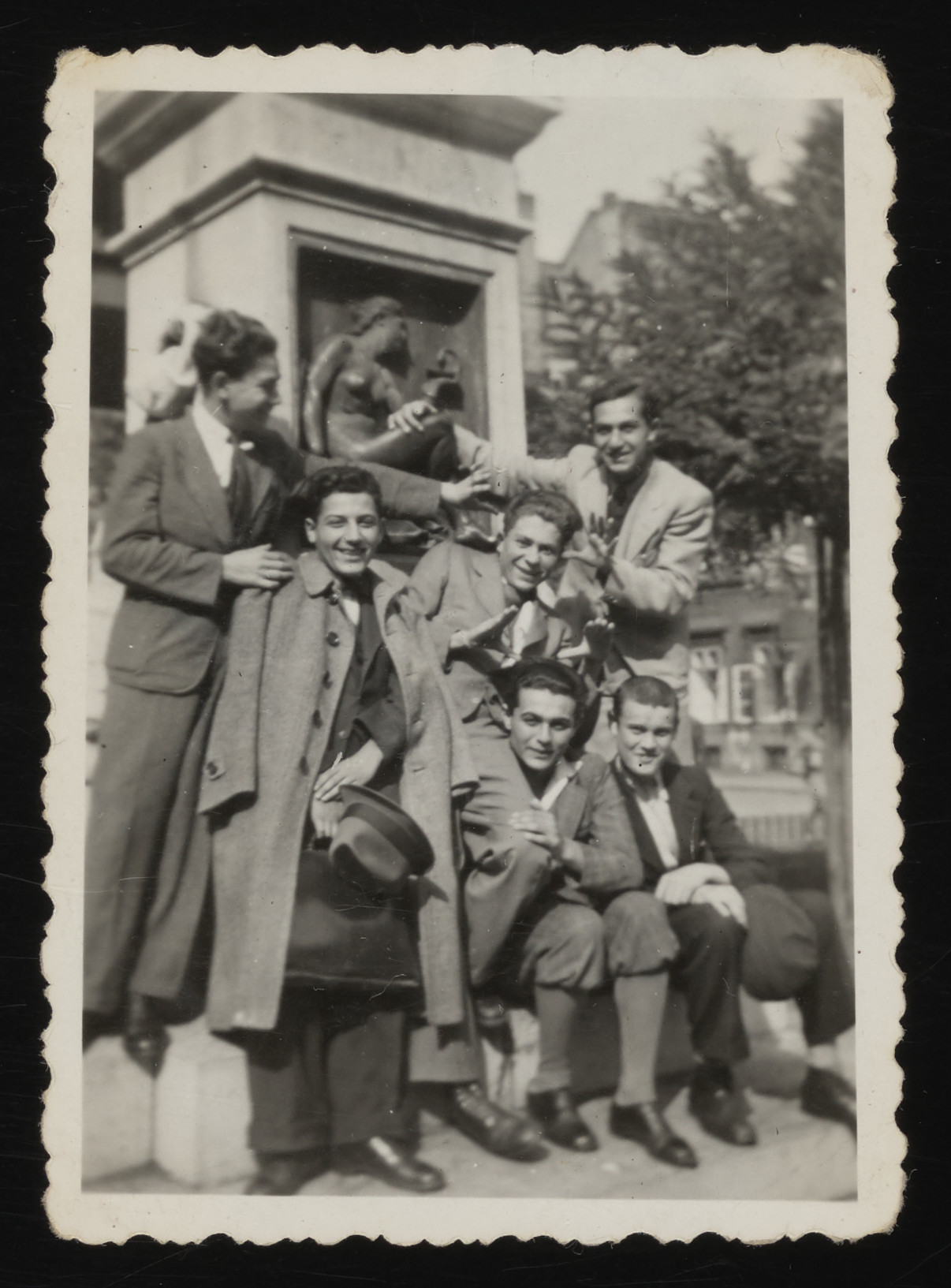 A group of Hungarian rabbinical students pose next to a statue in a public square in Budapest.  Among those pictured is Paul Ornstein (seated on the left).
