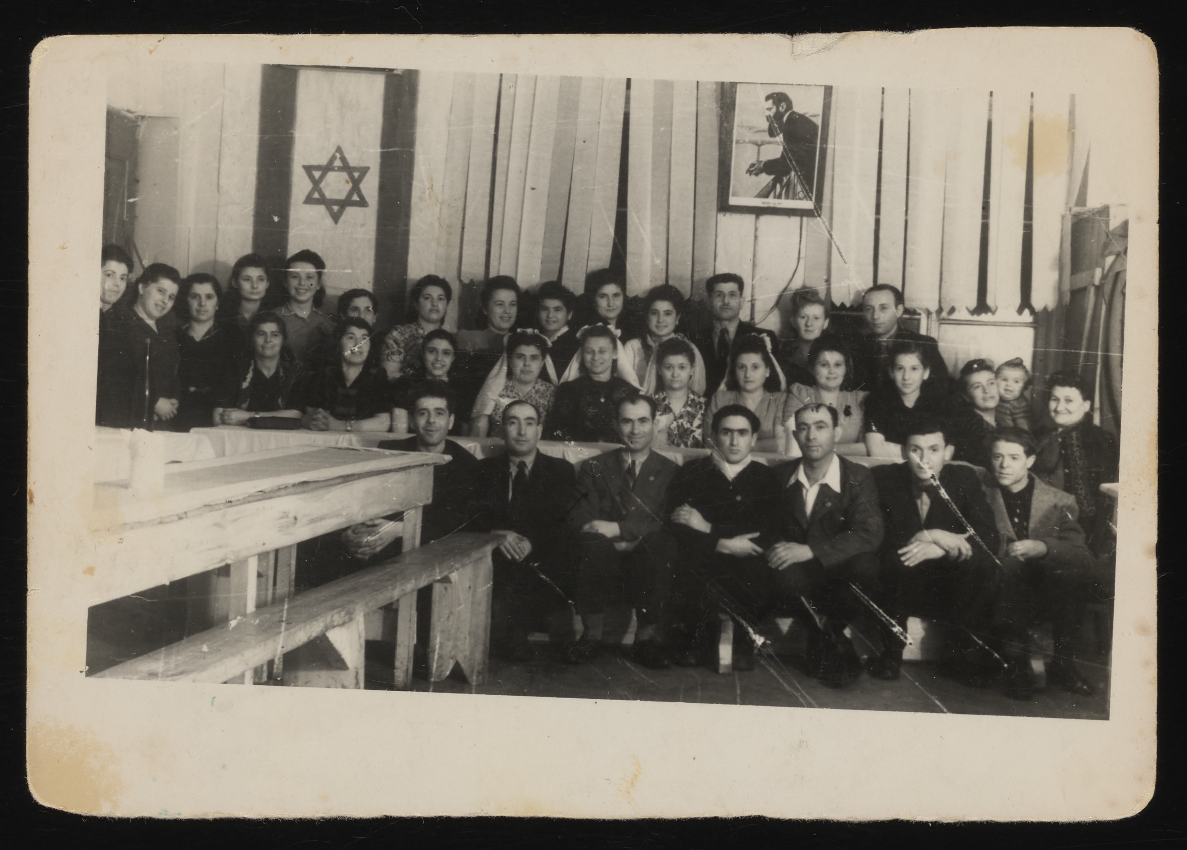 Members of Kibbutz Hatikvah in the Hofgeismar DP camp celebrate the wedding of four couples.  Among those pictured is Dora Kohl from Lvov holding her daughter Miriam. Standing third from left is Leah Rozow Tagfogel (Day).