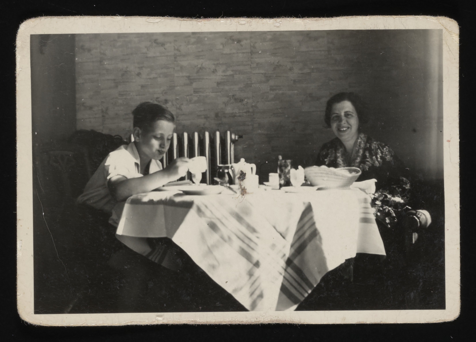Olga Loeb and her son, Hans, sit at a table set for tea.
