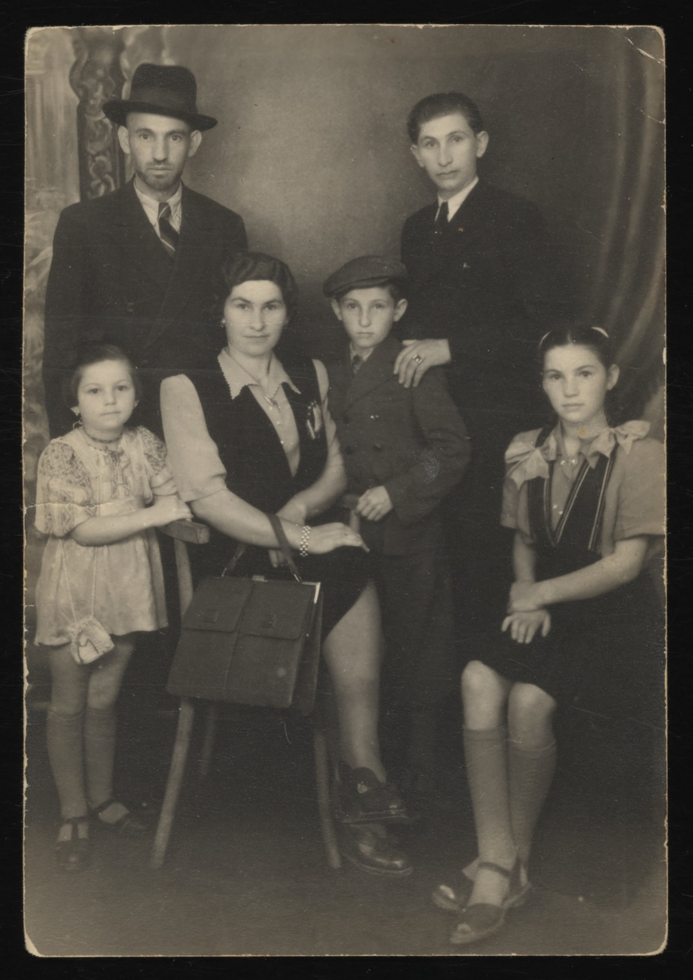Postwar studio portrait of the Spitzer family.  Pictured from left to right are Lily, Anton, Fany, Nathan, Simcha Wax (a maternal cousin) and Sara Spitzer.