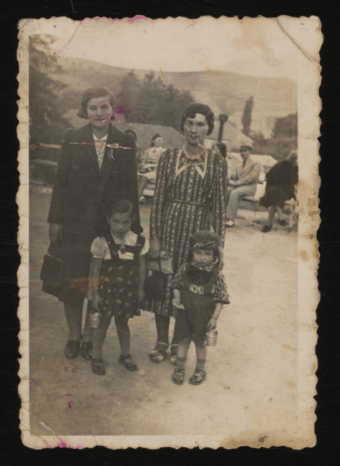 Two Romanian Jewish sisters pose with two young children in a park.  Pictured are Chana Wax, Fany Spitzer, Sara and Nathan Spitzer.