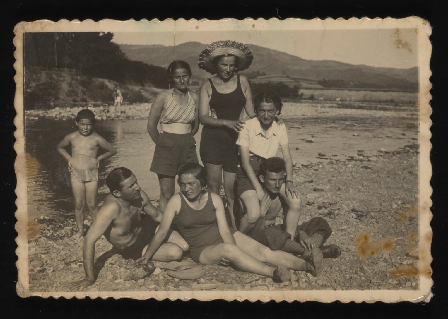 A group of friends from Drohobycz goes swimming on either a lake or a river.  Seated in front are Jacob Drimer and his sister-in-law Rywka Gruber.