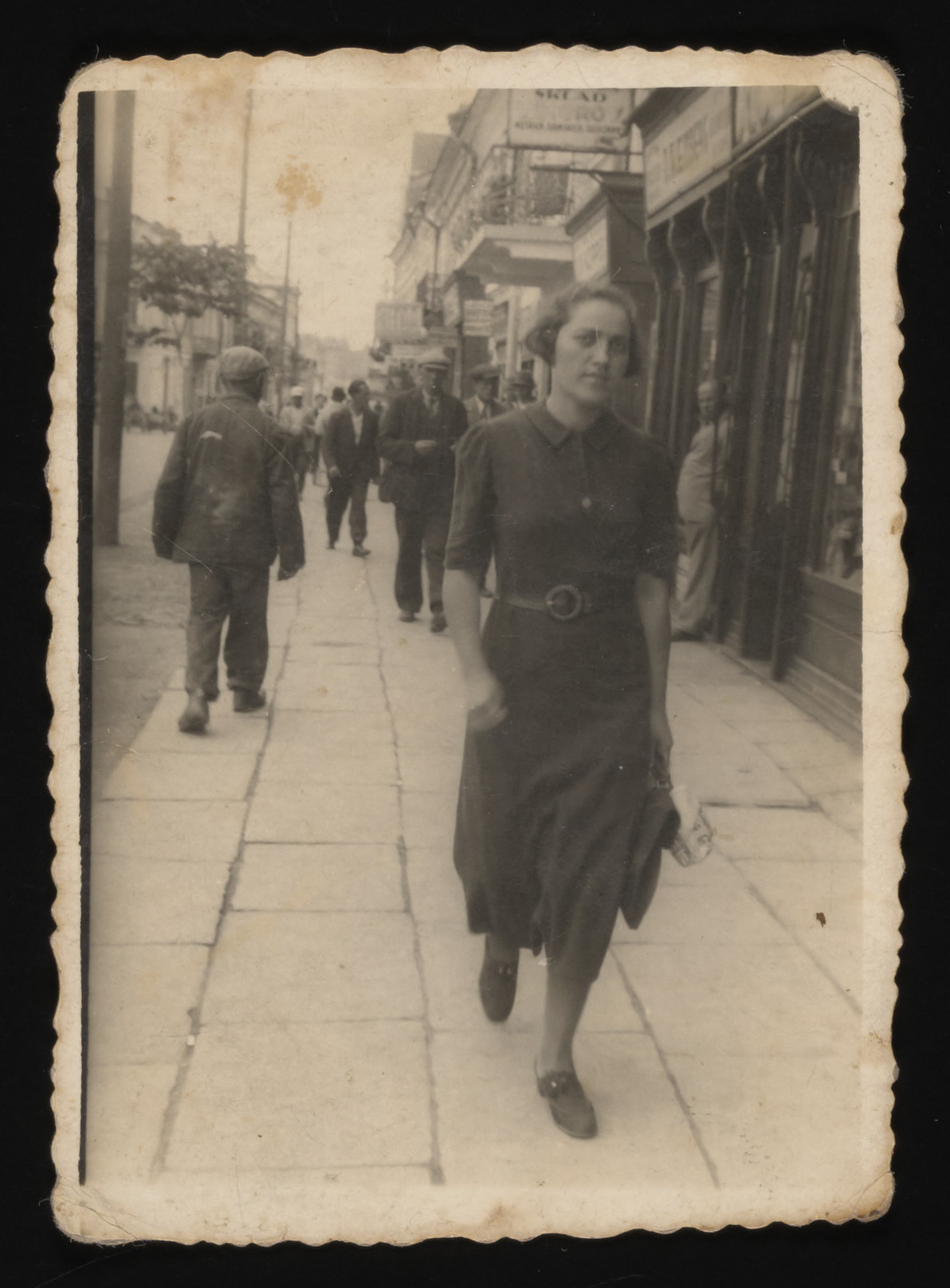 Rywka Gruber (aunt of the donor) walks down a street.  She was killed shortly after the German invasion of Eastern Poland in 1941.