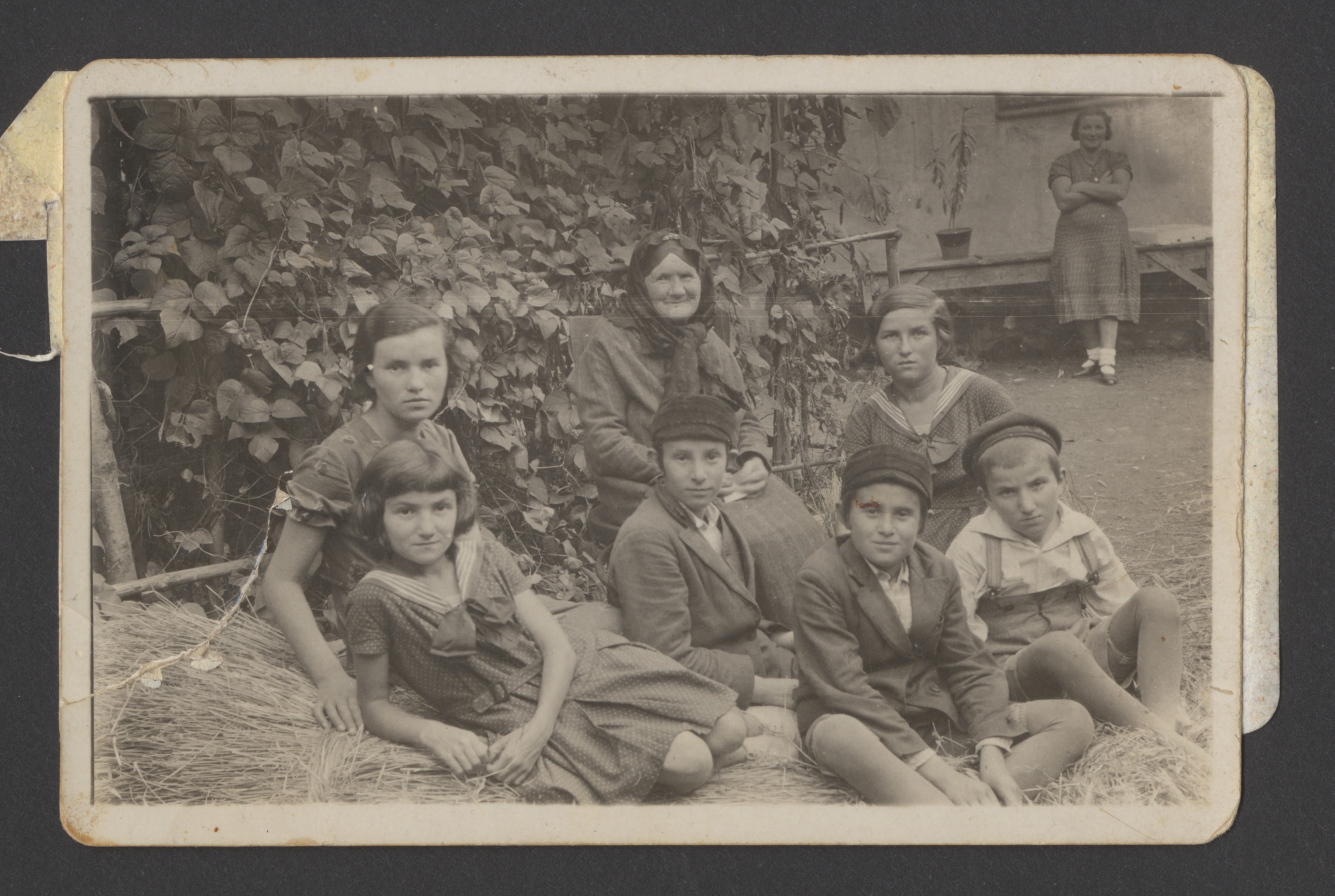 A Polish Jewish family gathers for a photograph in the backyard of their home in Nowy Sacz.  Pictured is Miriam Ullman (back, center) with her grandchildren:  siblings Blima (far left), Moishe (center), and Mayer Spiro (front, second from the right); and siblings Sally and Deborah (wearing sailor dresses), and Yoel Ullman (far right).