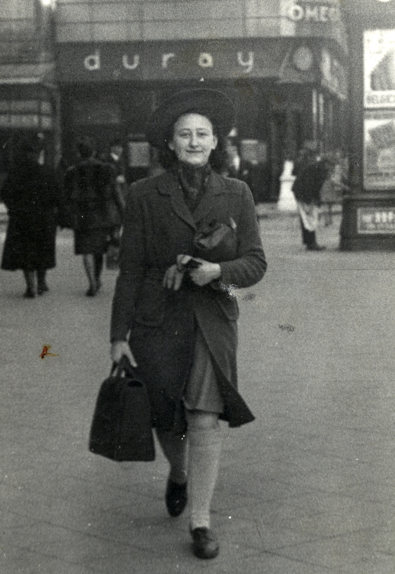 Eva Isboutsky walking down the street, covering the Star of David badge that she has been forced to wear.