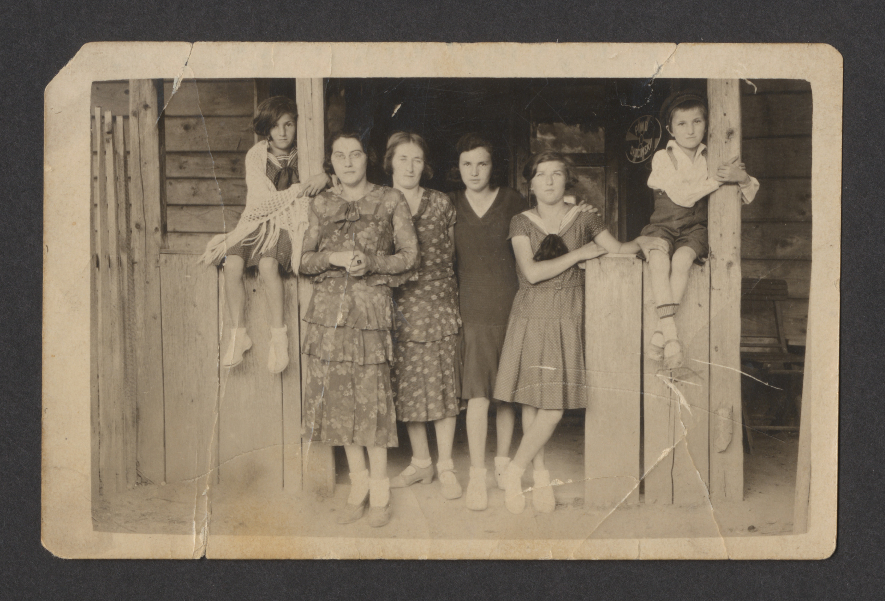A Polish Jewish family gathers on a porch for a photograph.  Among those pictured are Blima Spiro (second from right) and her cousin Yoel Ullman (far right).