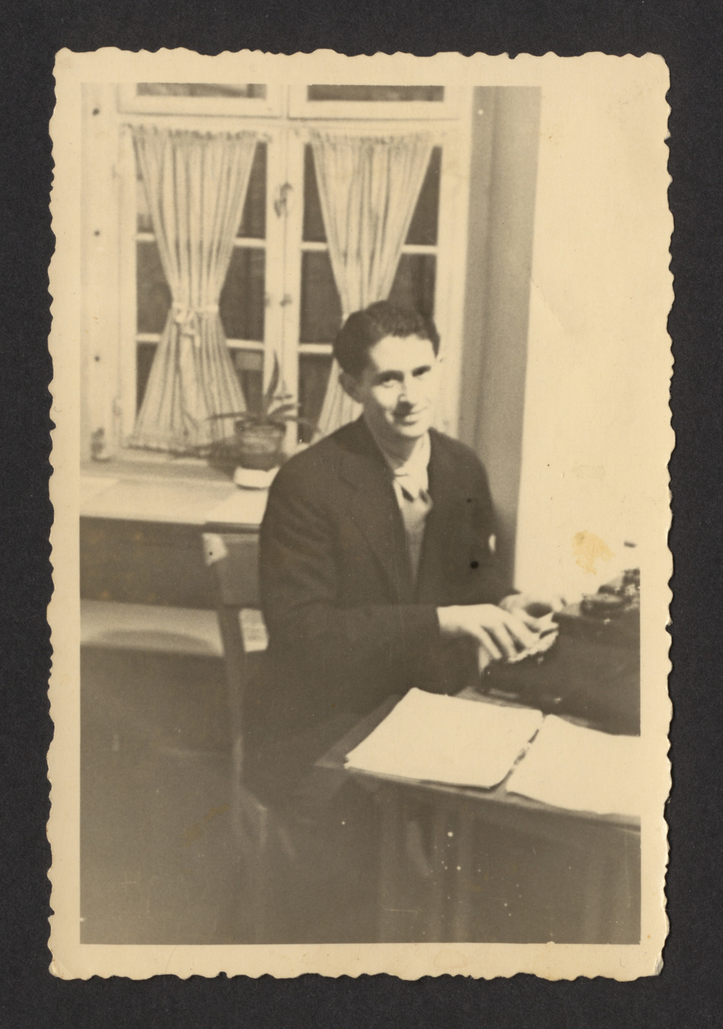 A Polish Jewish displaced person is seated at a typewriter at the Schwaebish Hall DP camp  Pictured is Mayer Spiro.