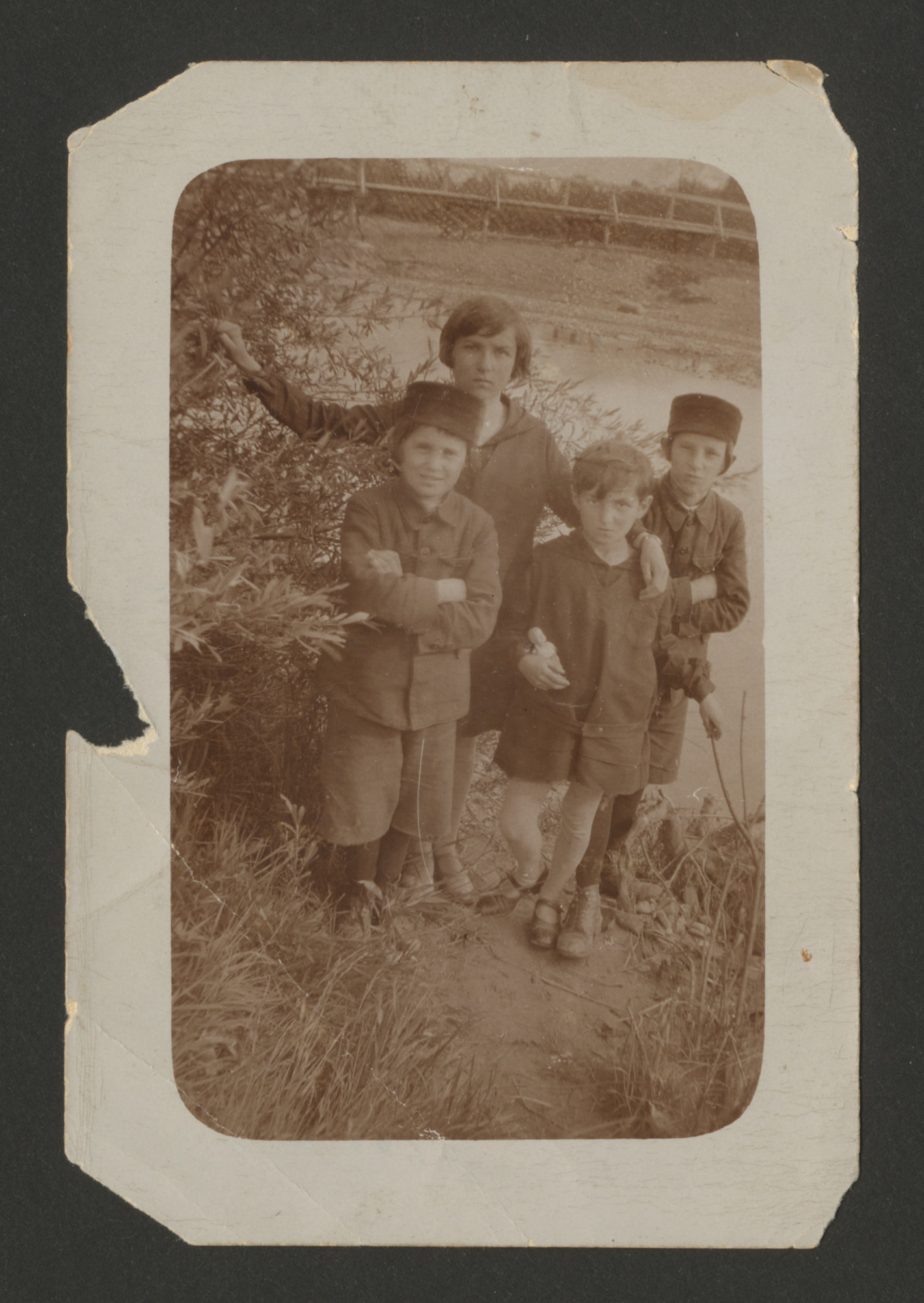 Children from a Polish Jewish family gather for an outdoor photograph.  Among those pictured is Mayer Spiro (far left).