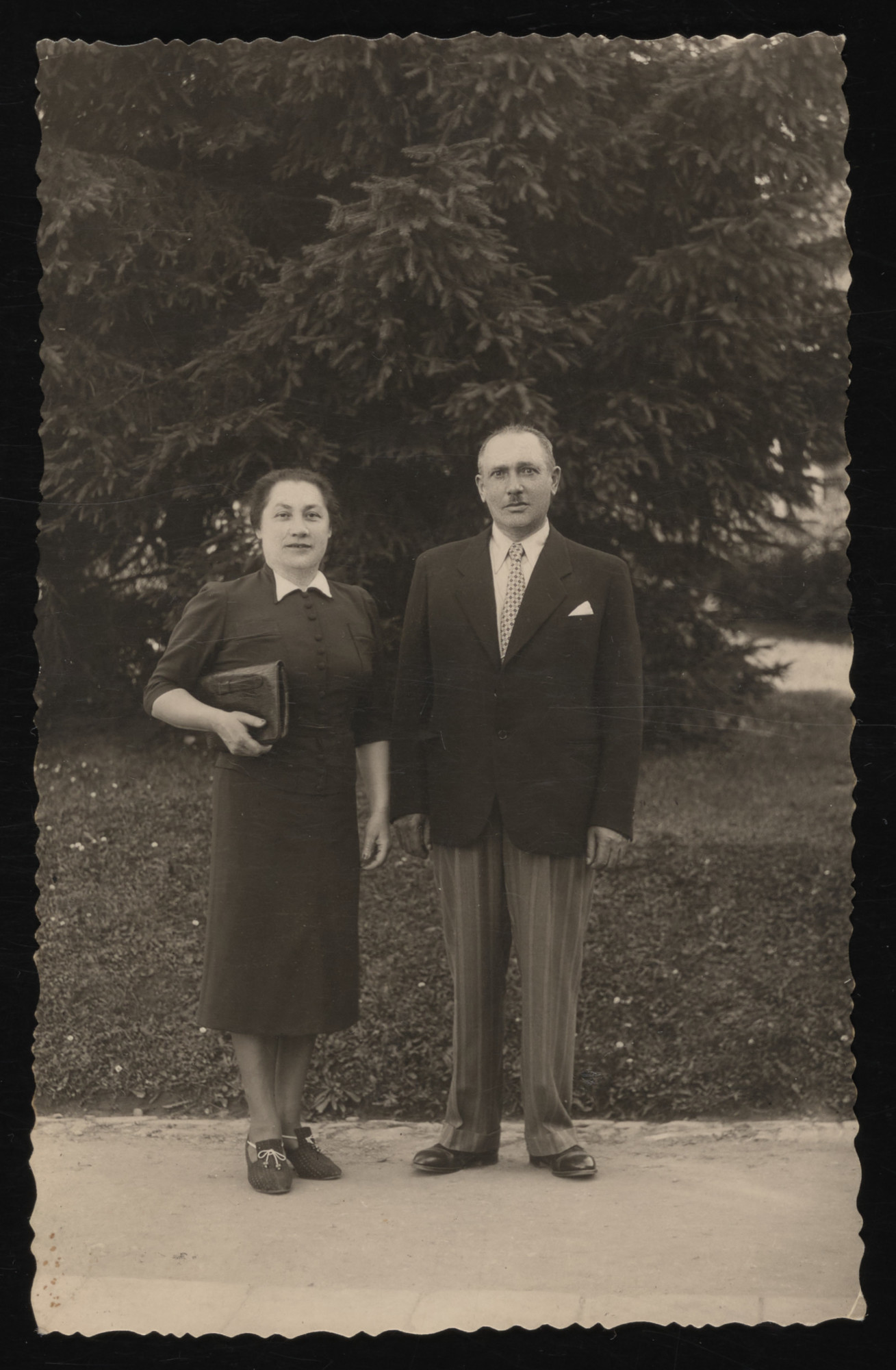 A Jewish couple poses outside at a spa in Krynica.  Pictured are Rozalia and Naftali Tabaczynski.