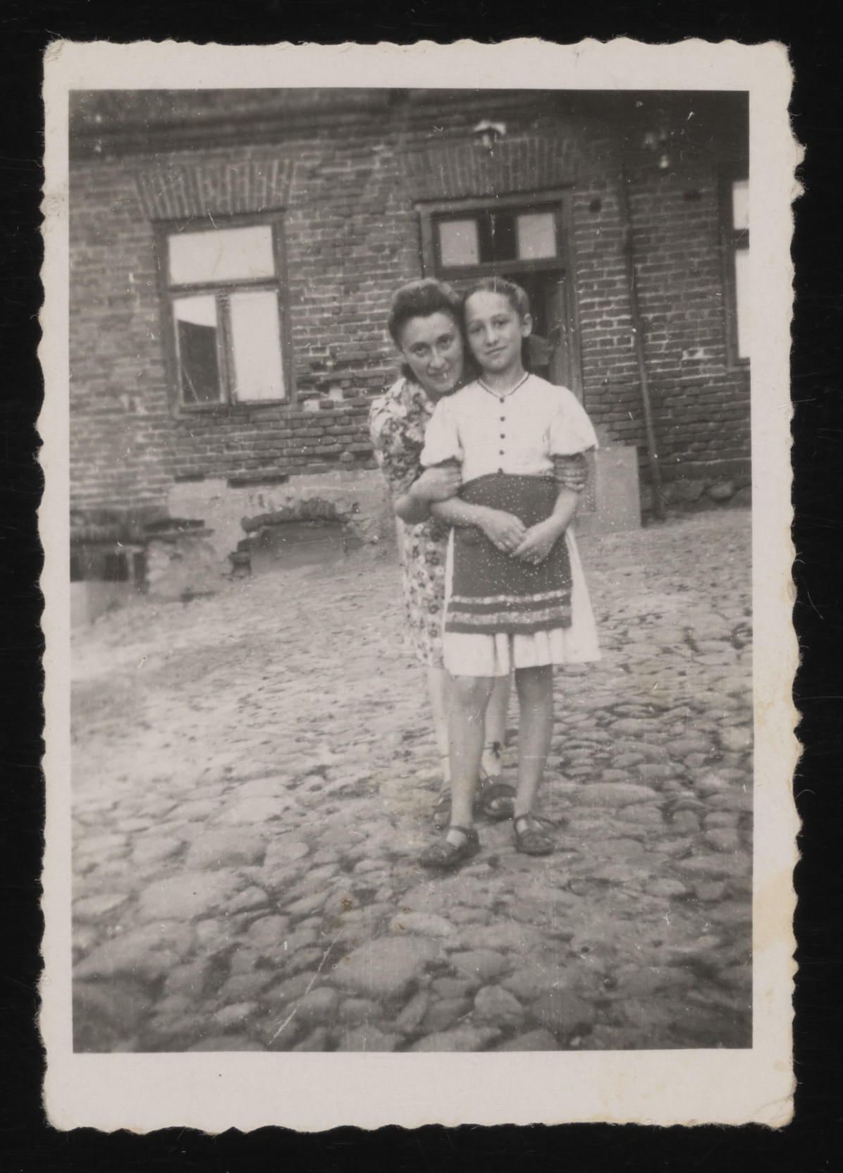 A Jewish mother and daughter pose in front of their house in Klodawa.  Pictured are Edzia Rachwalska (the cousin of Gina Tabaczynska) with her daughter, Sabina. They survived the war in hiding, along with Edzia's husband, Aron.