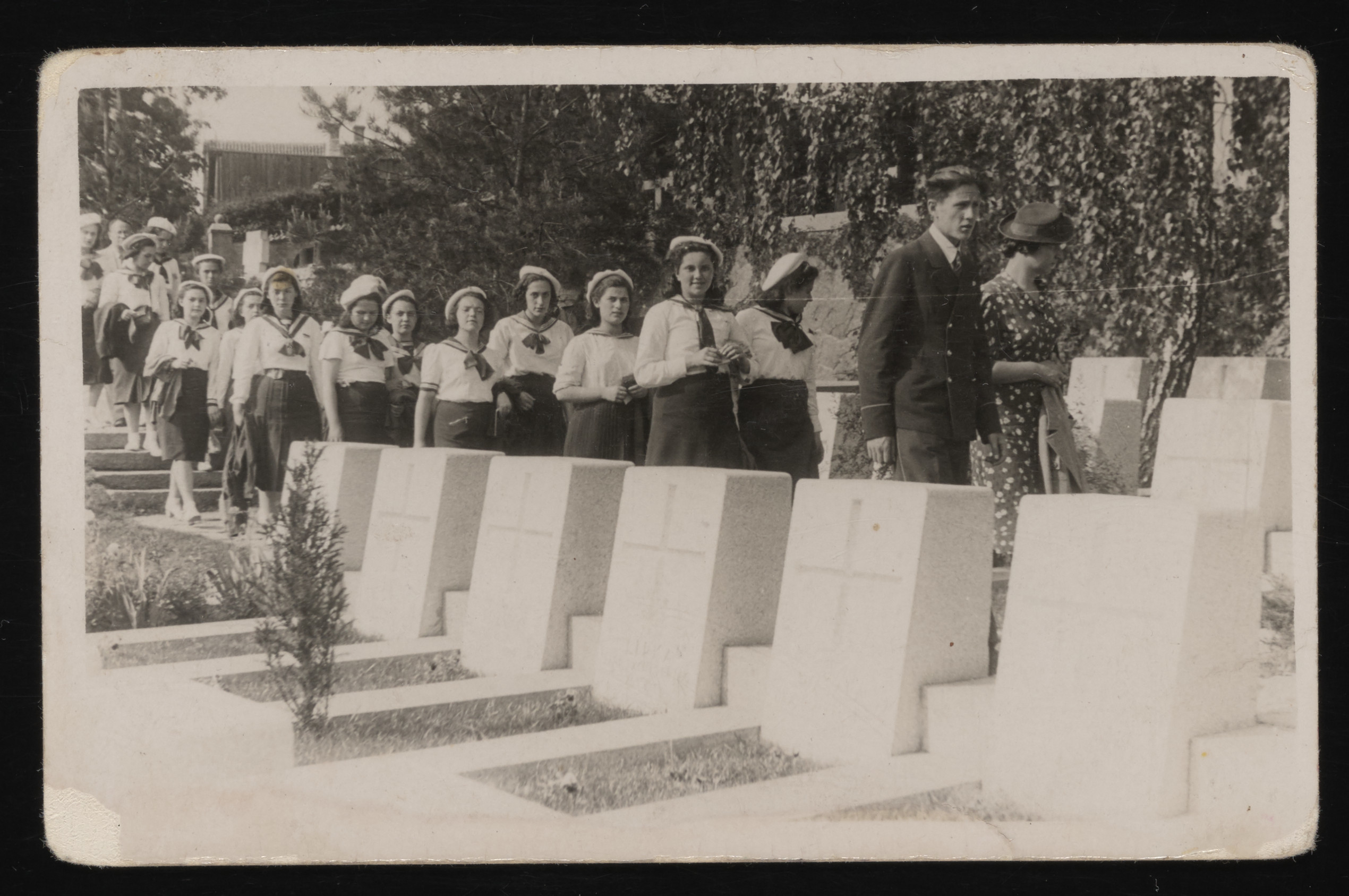 Students and teachers of the Mirlasowa private Jewish school in Warsaw, during a school trip to Vilna.    The group is visiting the cemetery where Josef Piulsudski's heart is buried.  Leading the column of students is Olga Lewinska, the Latin teacher.  Behind her are Ziuta Szczecinska, and Hanka Ginsburg. Gina Tabaczynska is third from the left.  Among the other students pictured are: Joasia Rotbard; Dzunia Uczen and Mirka Lejtes.
